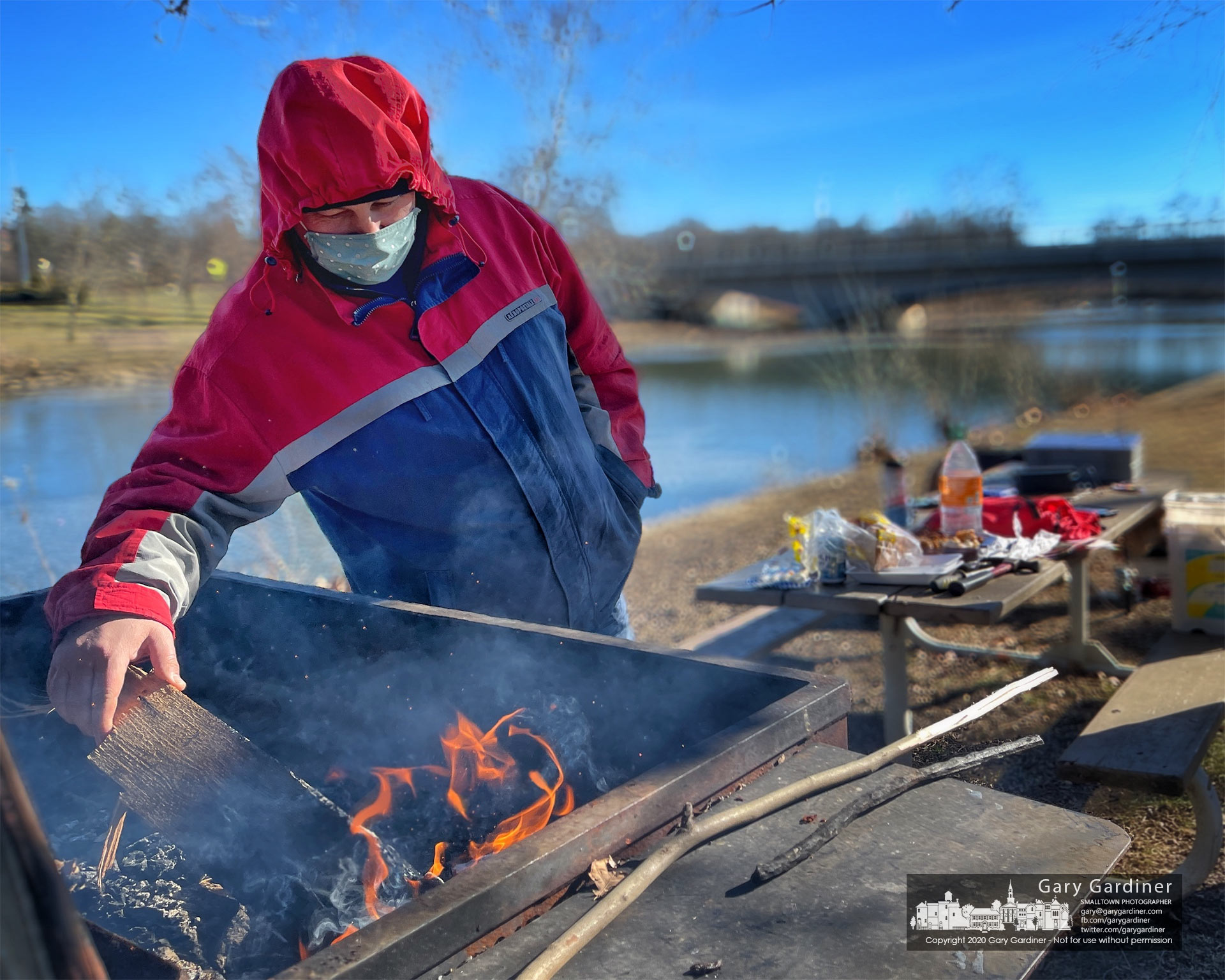 A fisherman feeds kindling into the grill behind the old Senior Center on Alum Creek as he waits for his friend to reel in a fresh fish for the fire. My Final Photo for Jan. 23, 2021.