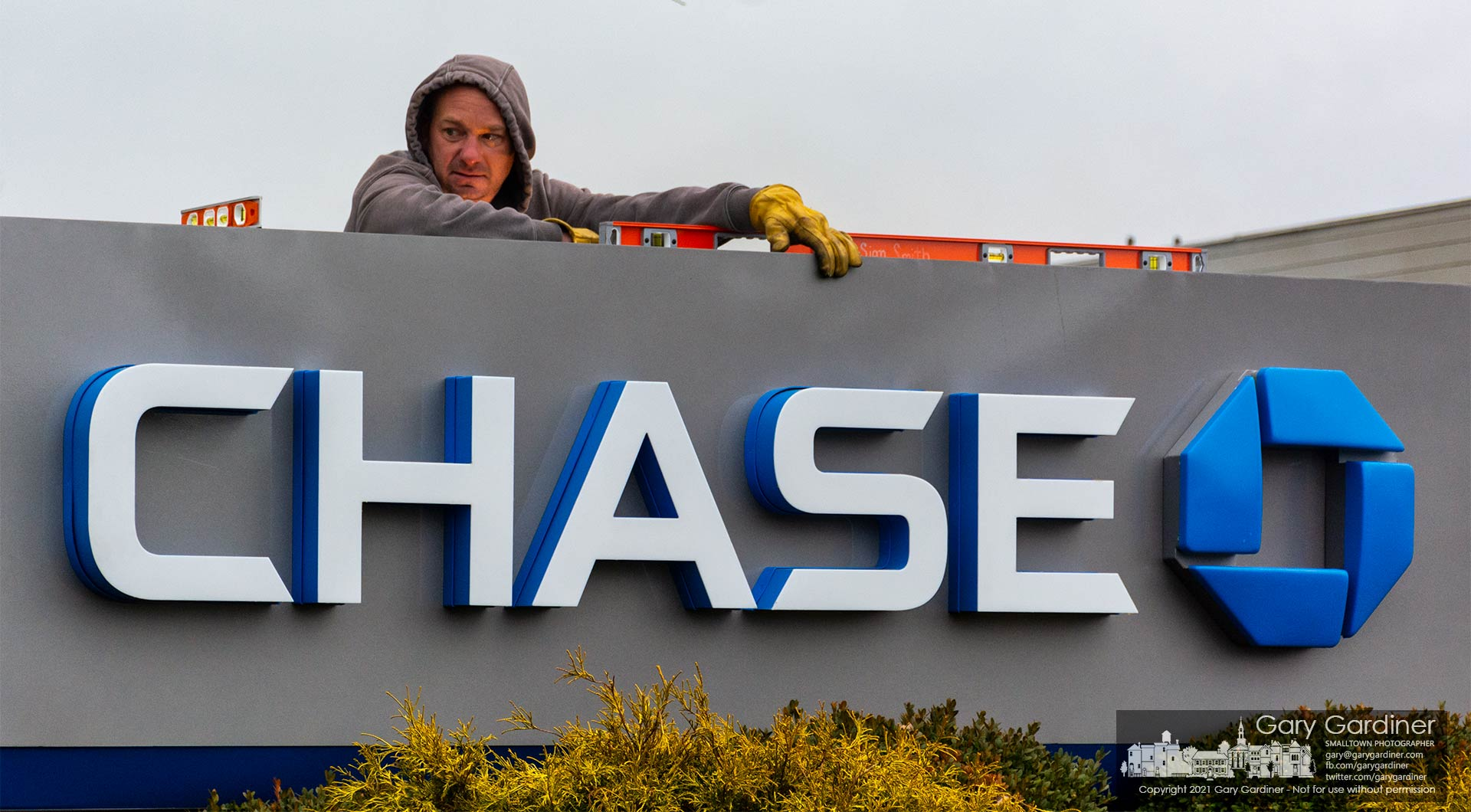 A worker diverts his eyes from the lights of a welder attaching the new Chase Bank sign to its pedestal on Huber Village Parkway. My Final Photo for Jan. 6, 2021.