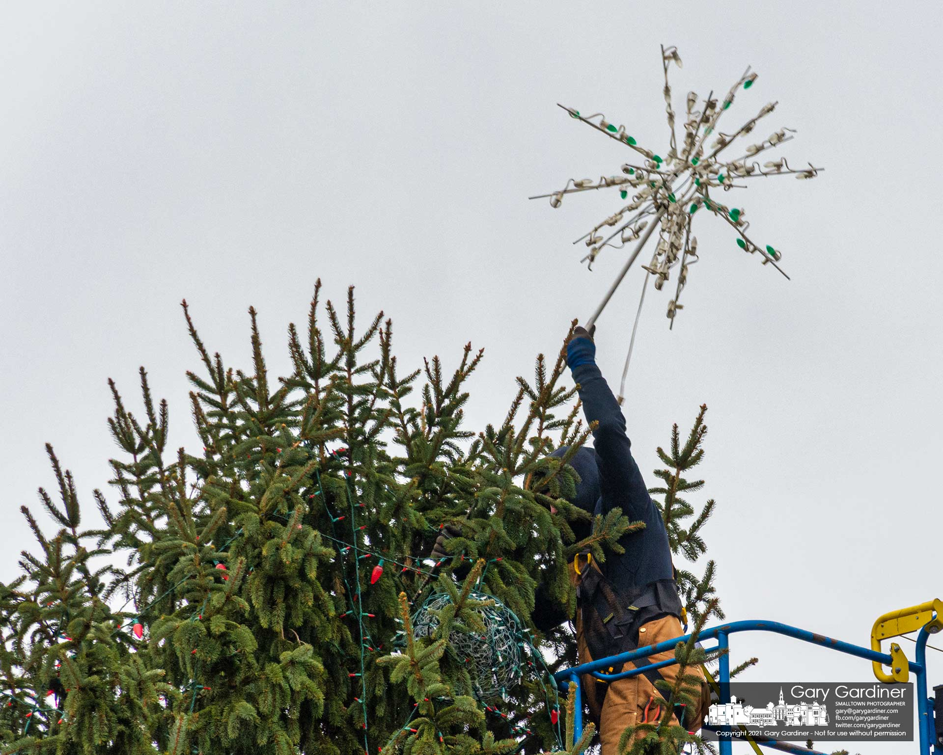 A city park worker removes the star from atop the Christmas tree on the civic green at city hall marking the end of the holiday season for a portion of Uptown. My Final Photo for Jan. 4, 2021.