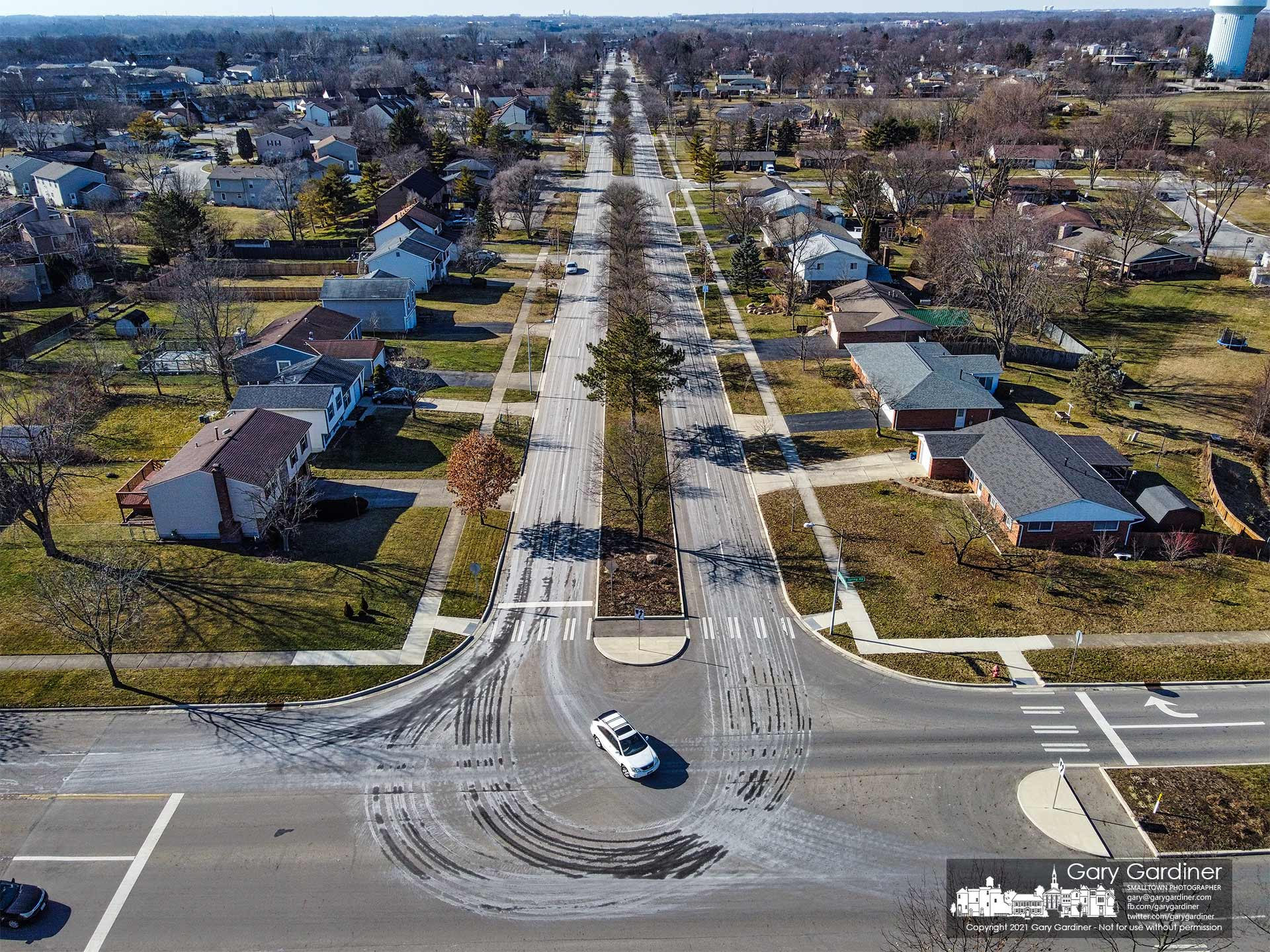 Cars travel through the intersection of Spring Rd. and Huber Village Blvd. over the drying spray of snow-melting brine sprayed by the city in anticipation of a weekend snowstorm. My Final Photo for Jan. 29, 2021.