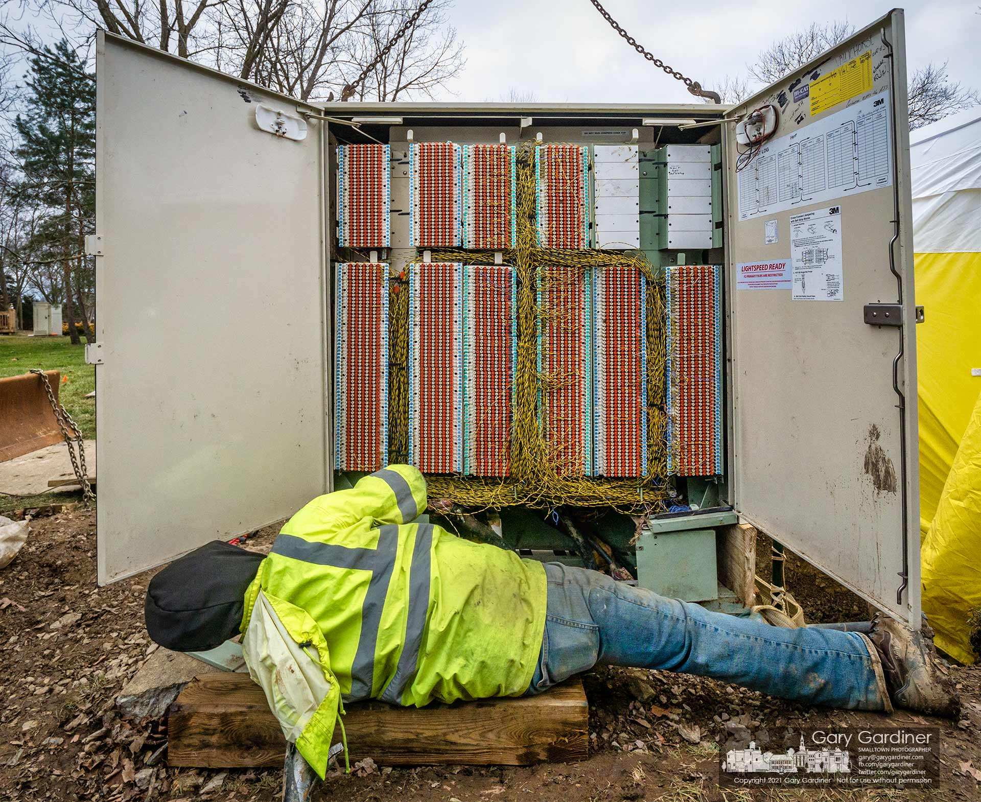 A technician adjusts the placement of a section of the ATT copper cable connection box on Huber Village Dr. during repairs for the structure damaged by a car crash. My Final Photo for Jan. 7, 2021.