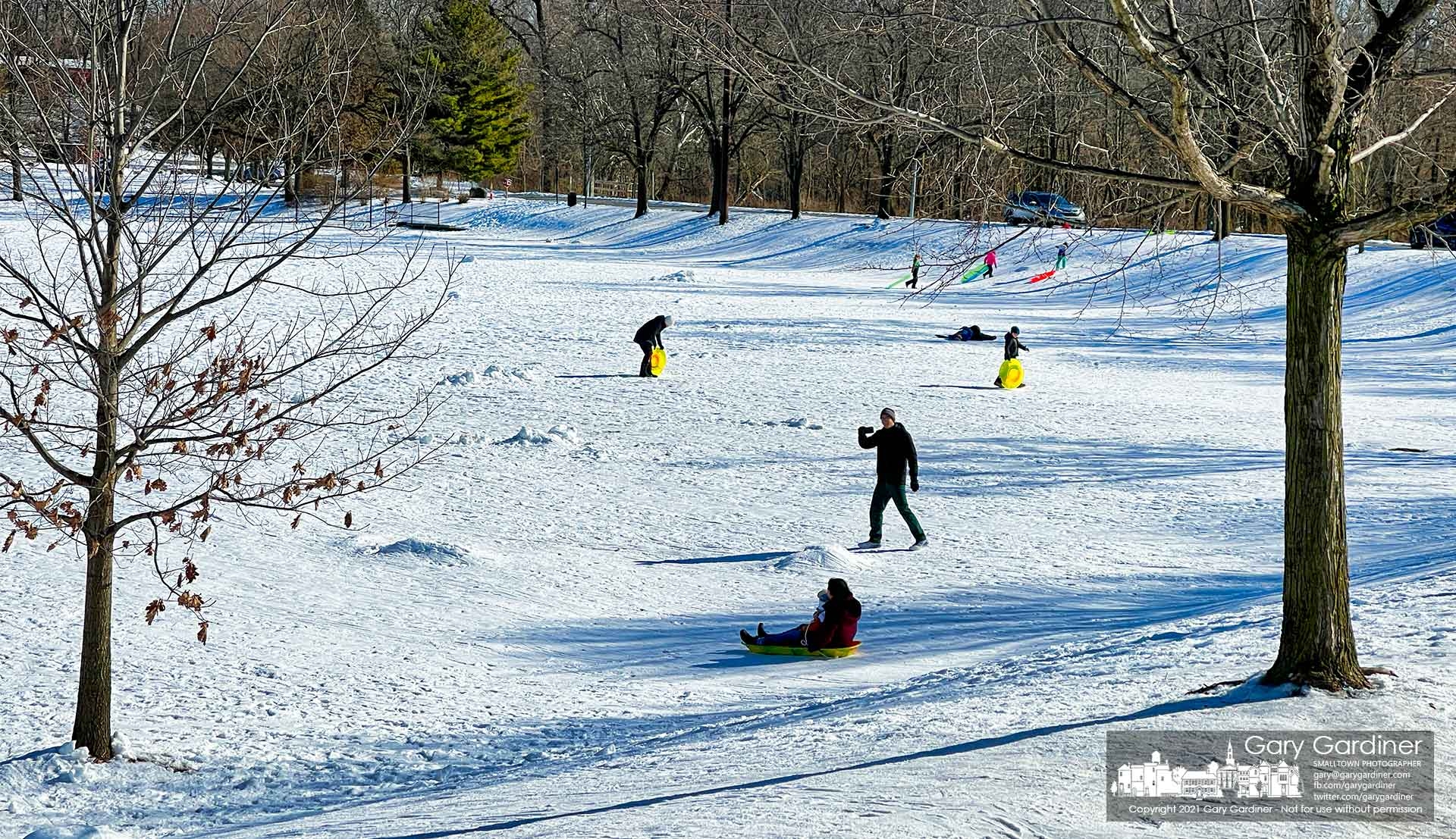 A father runs down the snow-covered incline at Alum Creek Park to make a video of his wife and child riding a sled on the packed snow. My Final Photo for Feb. 6, 2021.