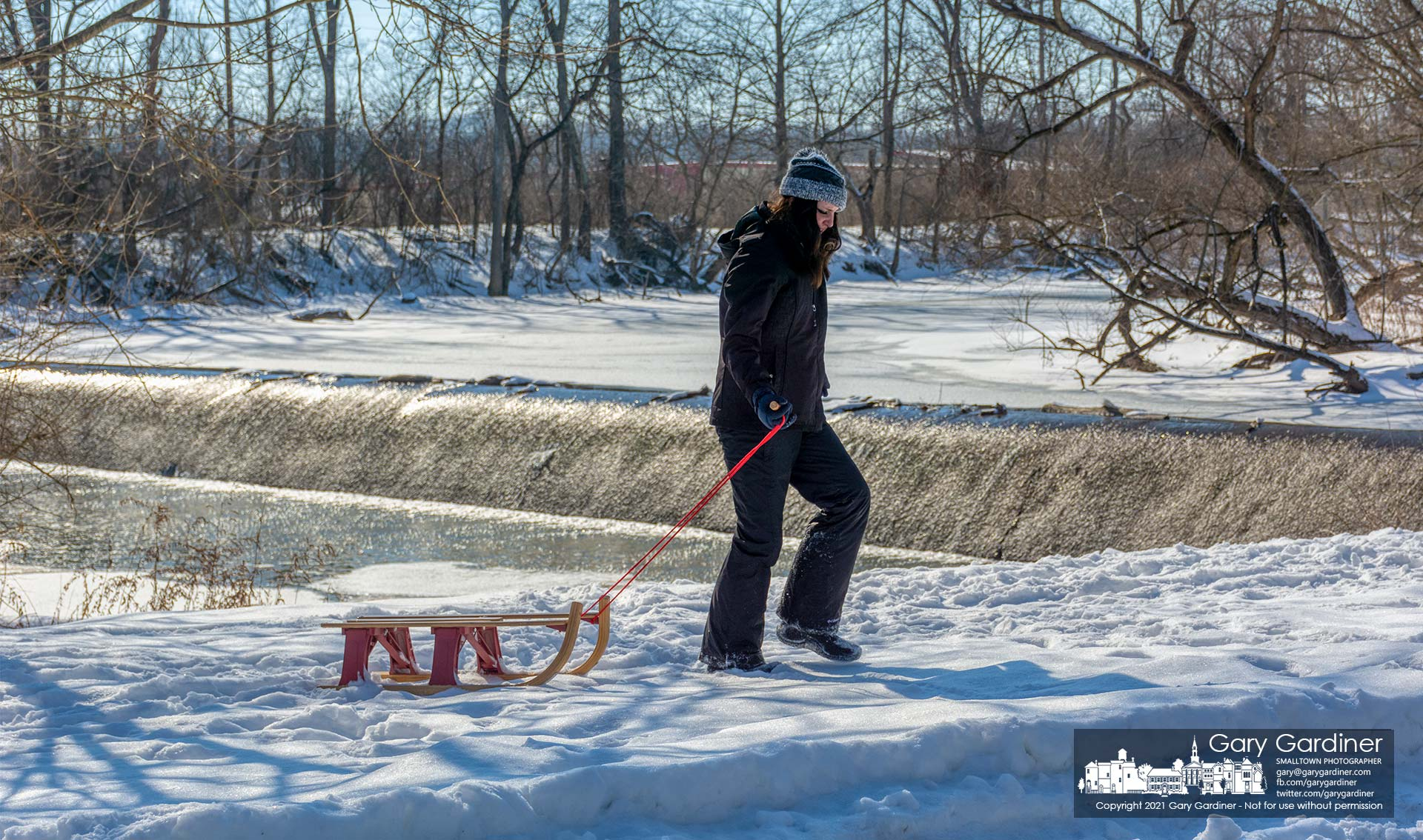 A young woman drags her sled after she and a friend explored the snow-covered island just below the low-head dam at Alum Creek North. My Final Photo for Feb. 20, 2021.