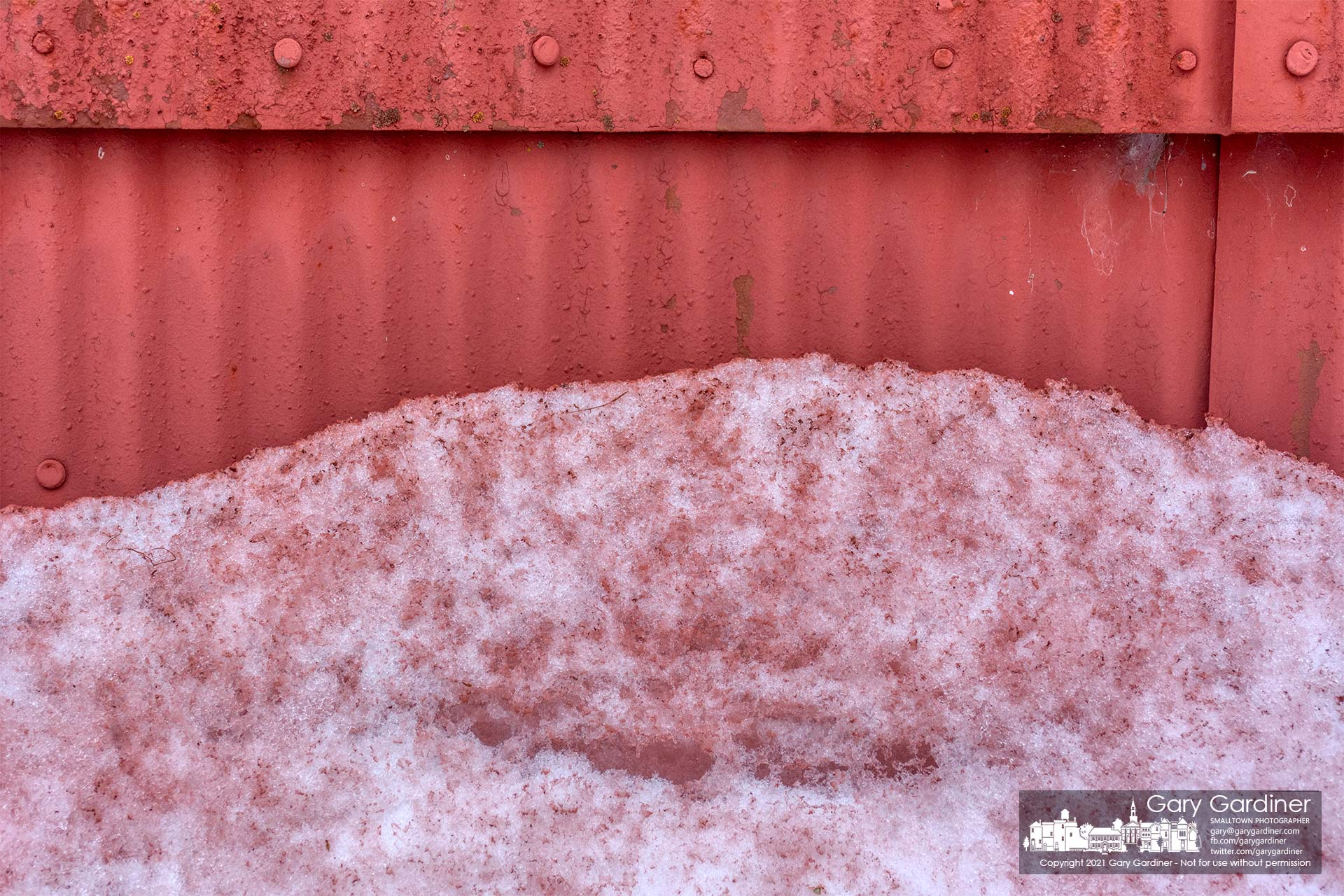Banks of snow surround the barn on the Braun Farm are colored red where paint from the building's roof flaked off after ice and snow from the recent storms weathered the old paint. My Final Photo for Feb. 22, 2021.