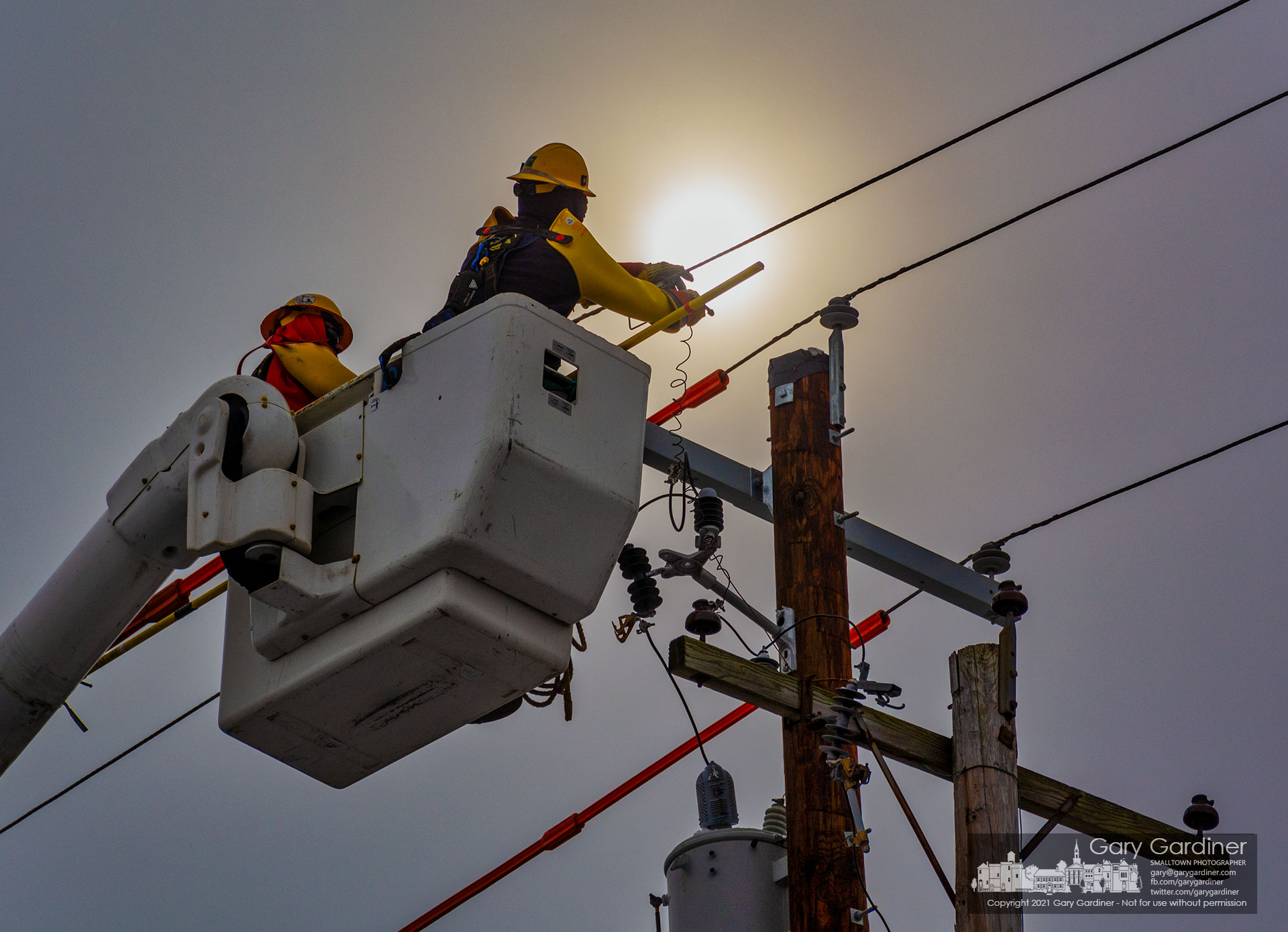 A city electric worker attaches wiring to power lines moved to a new utility pole on North State Street just north of Uptown. My Final Photo for Feb. 11, 2021.