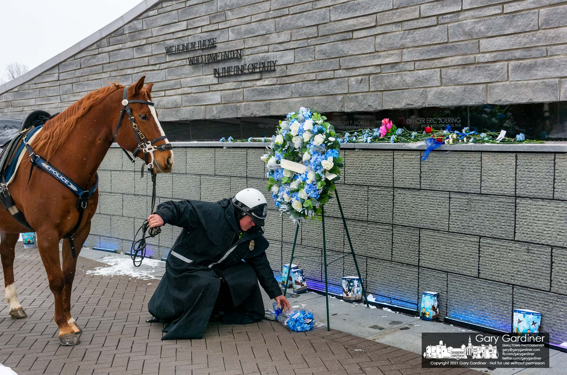 A Columbus Police Mounted Patrol officer lays flowers at First Responders Park in Westerville on the anniversary of the deaths of two officers killed while answering a domestic violence call. My Final Photo for Feb. 10, 2021.
