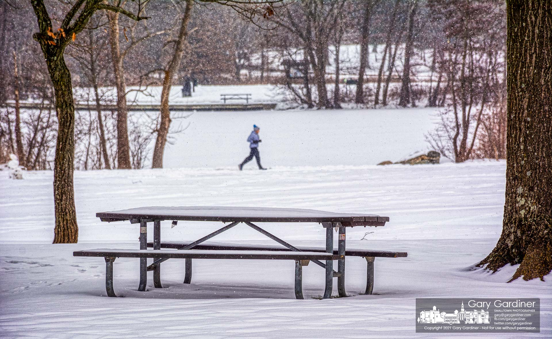 A runner travels along the trail past Schrock Lake at Sharon Woods Metro Park where the picnic tables wear a covering of snow as more is forecast for the week making picnics nearly impossible. My Final Photo for Feb. 13, 2021.