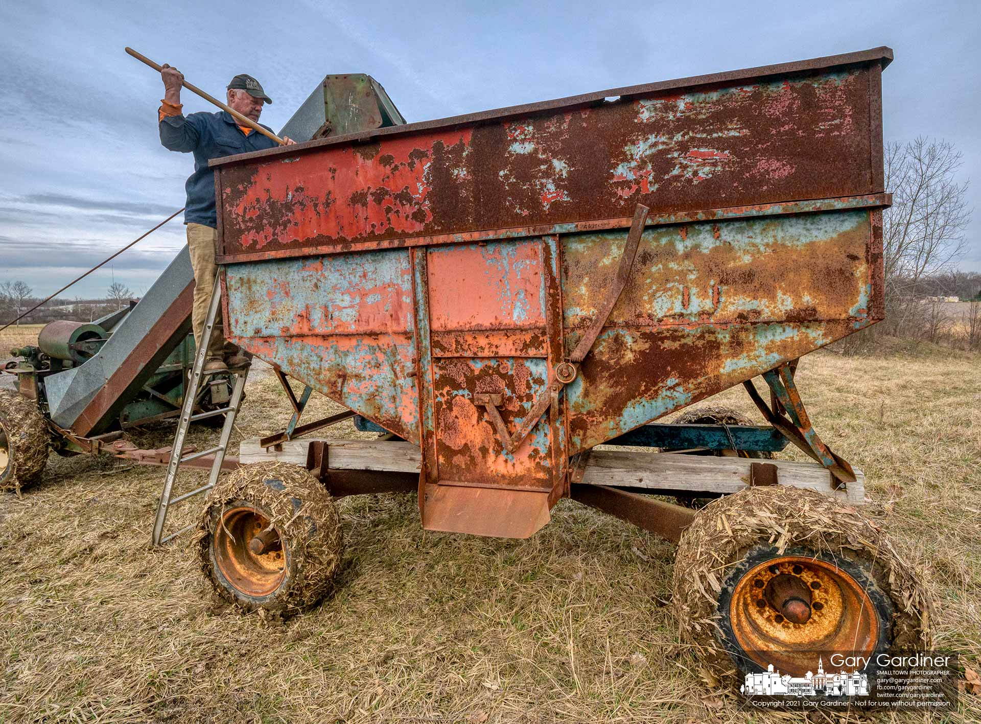 Kevin Scott rakes corn leveling it in the wagon he's using to complete the harvest on the Braun Farm. My Final Photo for March 14, 2021, π Day.