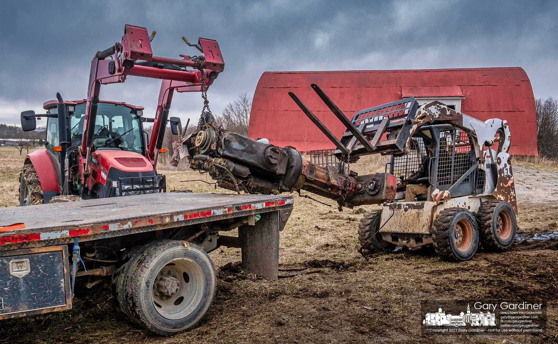 Using a tractor and a Bobcat, the GM engine and Oliver transmission from a Minneapolis-Moline A4T-1600 1970s-era tractor from the Braun Farm is lifted on a truck bed for transport to a scrap yard. My Final Photo for March 15, 2021.
