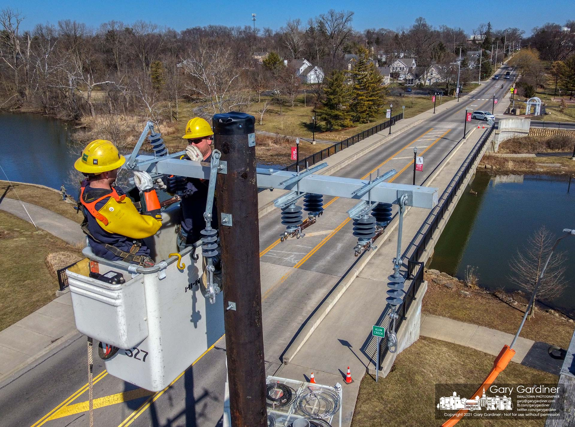 A city electric crew installs a crossbar on a new utility pole at the Main Street bridge where power lines will be directed underground as the nearby substation is upgraded. My Final Photo for March 3, 2021.