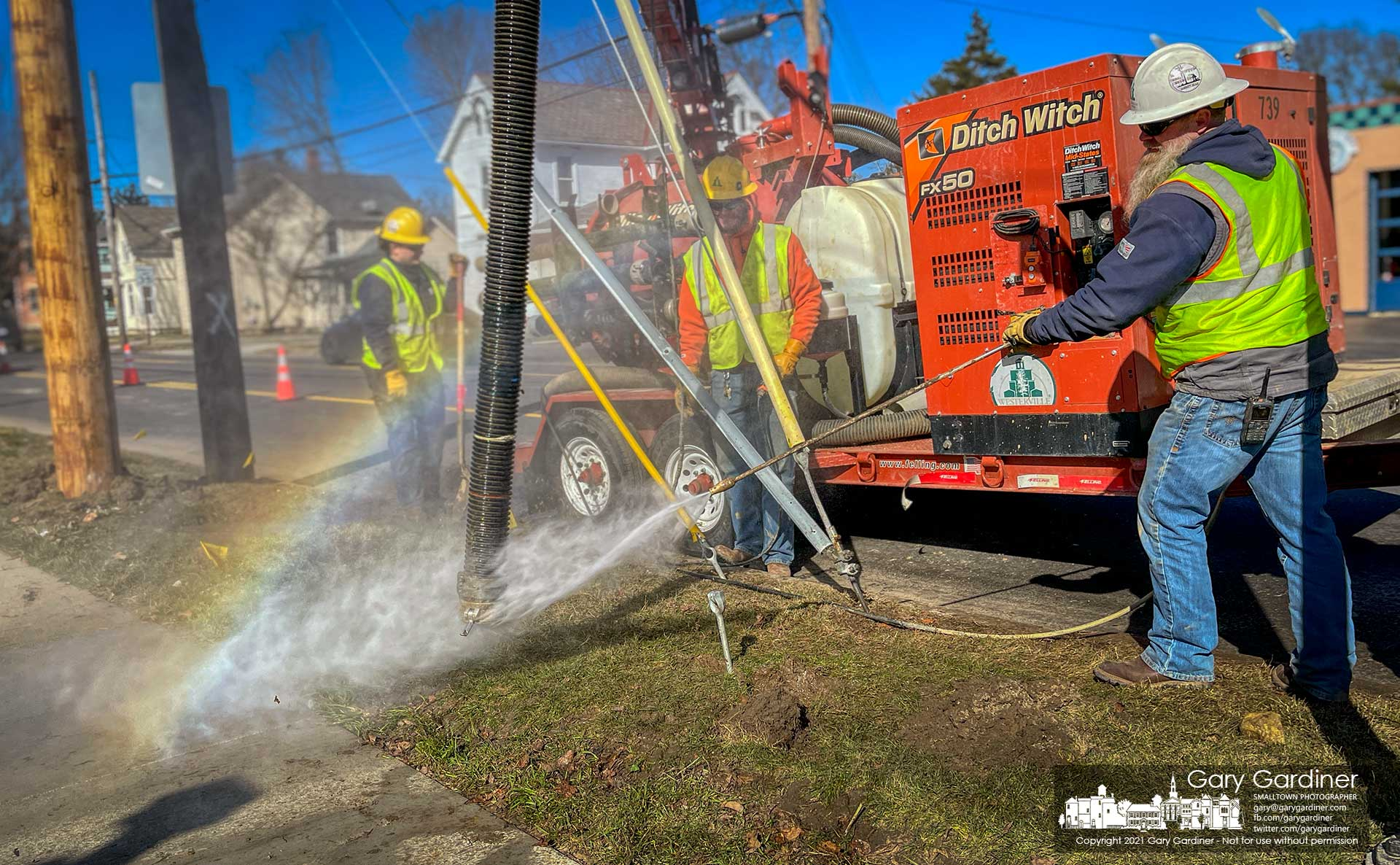 A city electric work crew creates its own small rainbow washing off a vacuum hose used to clear holes during the replacement of a utility pole in Uptown Westerville. My Final Photo for March 2, 2021.