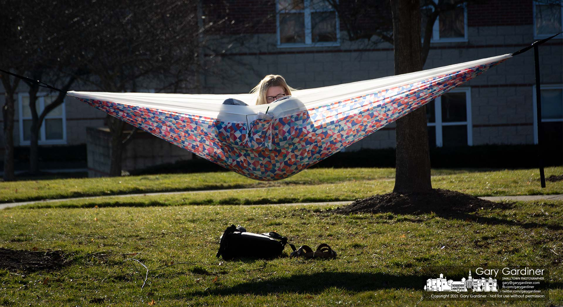 An Otterbein student reads in a hammock with her back warmed by the afternoon sun on the grassy plaza behind Towers hall. My Final Photo for March 6, 2021.
