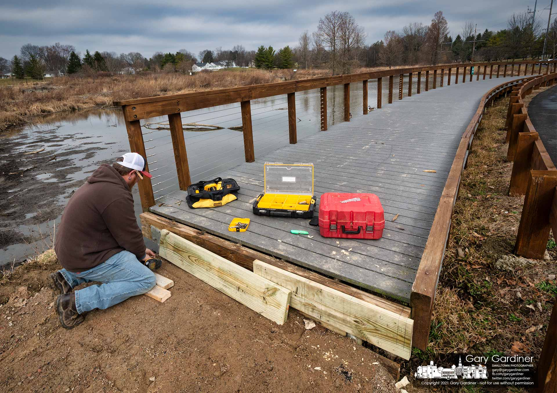 A carpenter attaches header boards to a section of the walkway at Highlands wetlands being rebuilt to create a ramp leading to the sidewalk. My Final Photo for March 16, 2021.