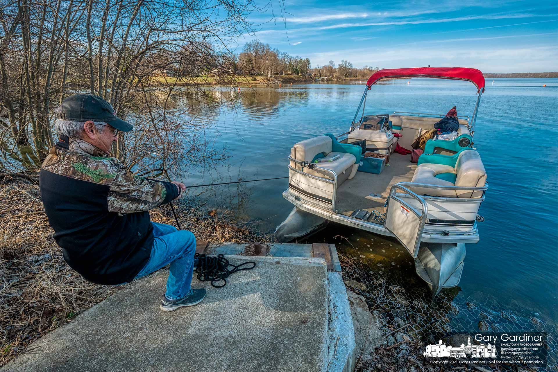 A boater pulls his pontoon boat close to shore for a temporary mooring for passenger offload after completing a test run putting hours on a new motor for the craft. My Final Photo for March 13, 2021.