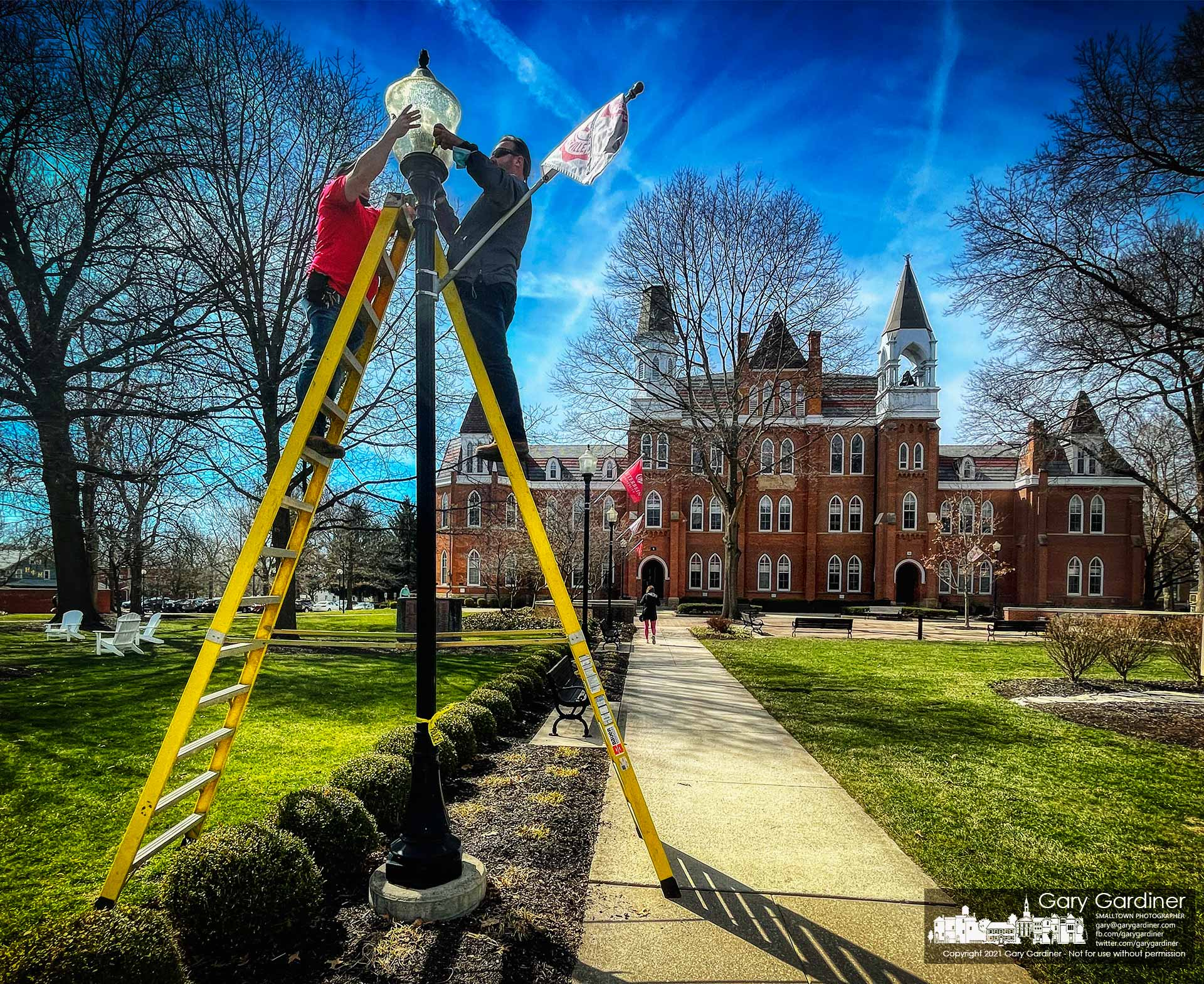 Otterbein maintenance workers replace a bulb in one of the lights illuminating the walkway to Towers Hall at the entrance to the school at the end of College Ave. in Westerville. My Final Photo for March 12, 2021.
