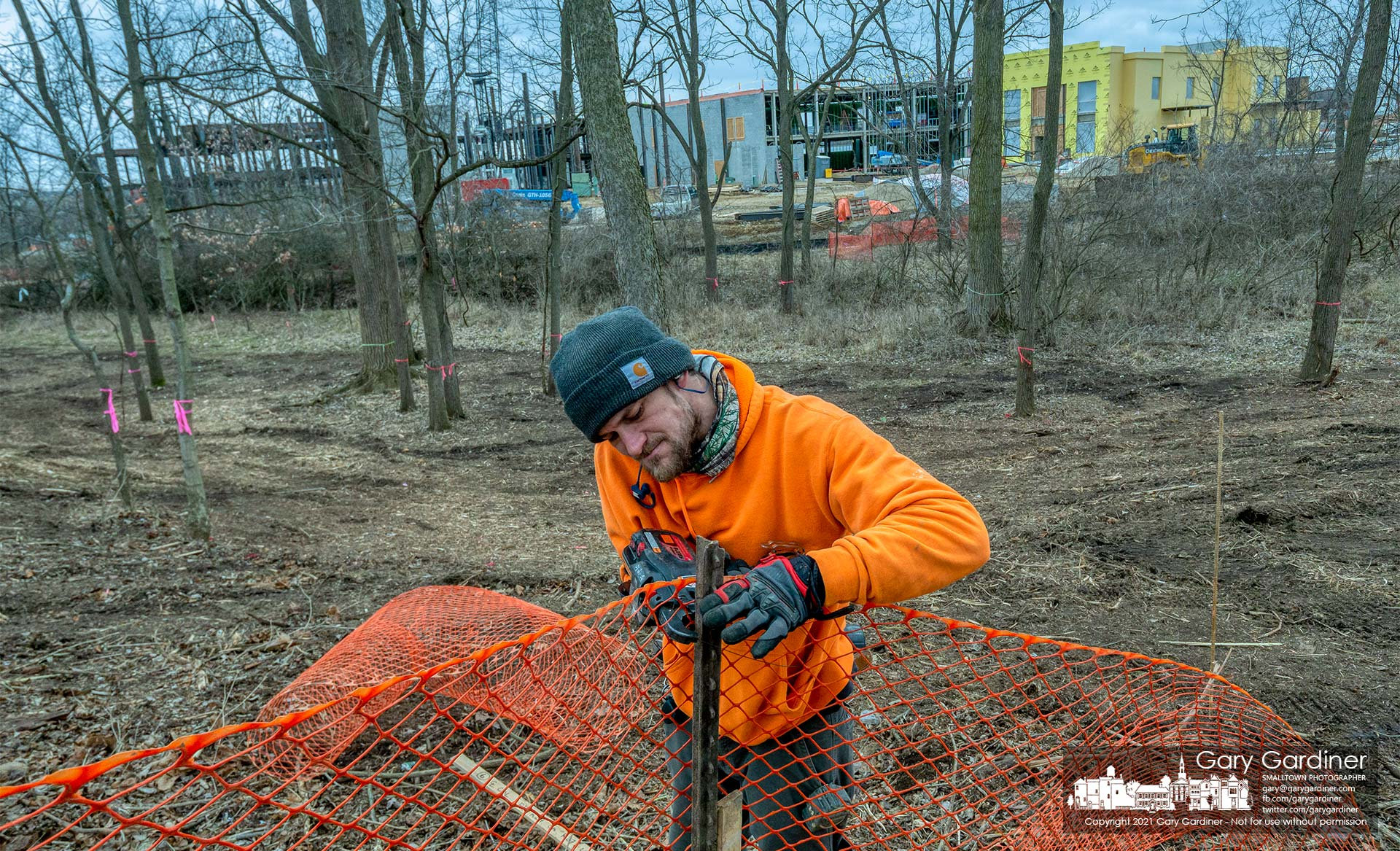 A worker builds a temporary safety fence around a section of the woods cleared at County Line and Africa Roads where a new skilled-nursing health care building is under construction. My Final Photo for March 4, 2021.