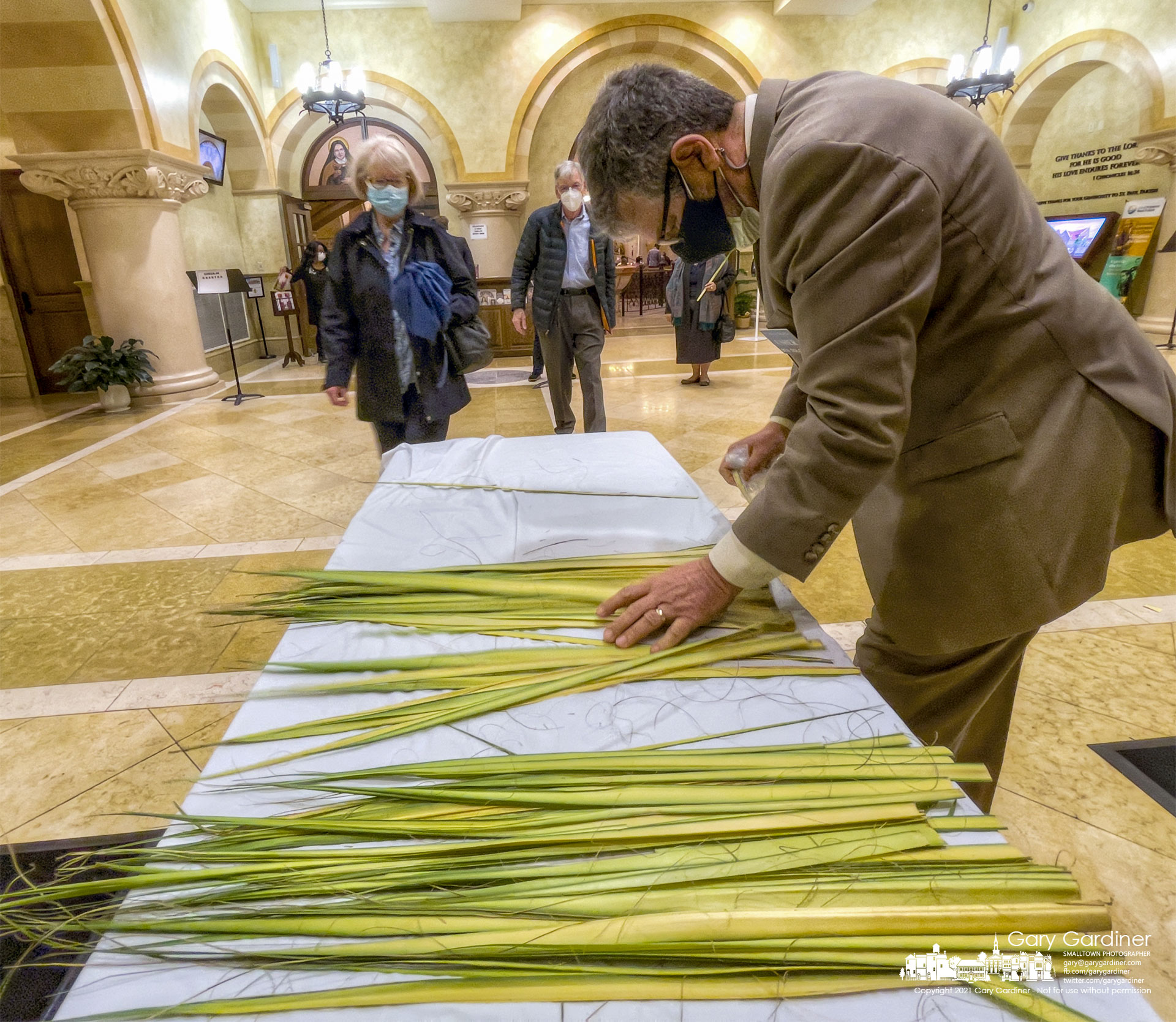 An usher at St. Paul the Apostle Catholic Church separates palm fronds for parishioners attending Palm Sunday Mass at the Westerville, Ohio church. My Final Photo for March 28, 2021.