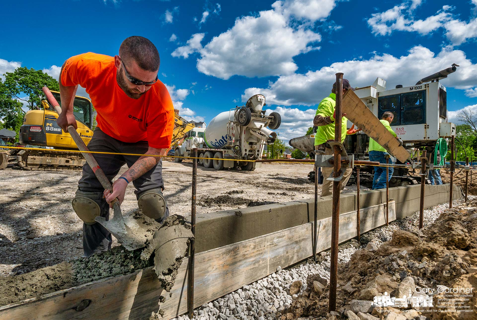 A worker removes machine-poured concrete gutter to level it for handicapped spaces in the new parking lot behind city hall. My Final Photo for May 11, 2021.