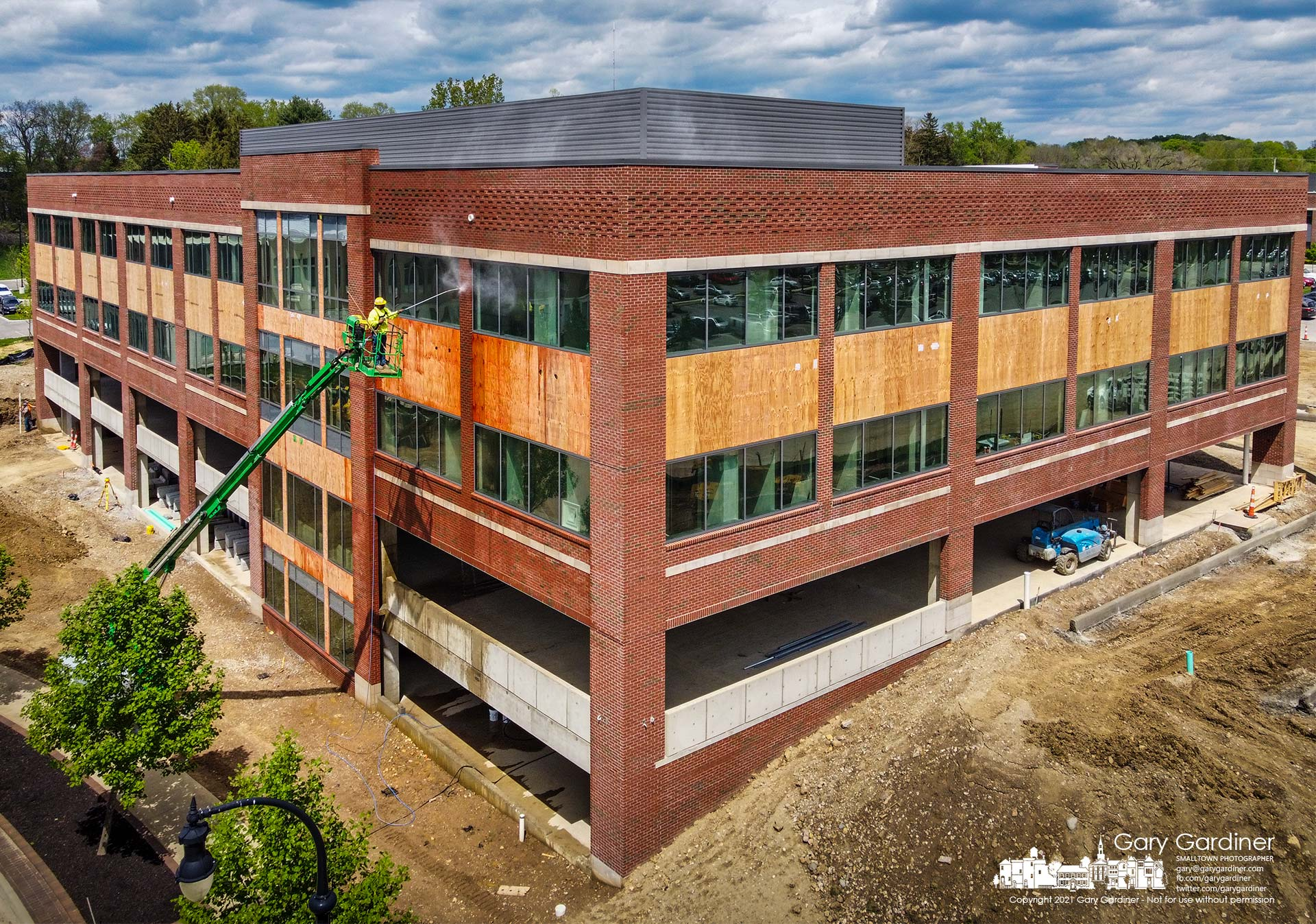 A work crew completes pressure washing the newly laid brick exterior of the third COPC building being built on Africa Road. My Final Photo for May 6, 2021.