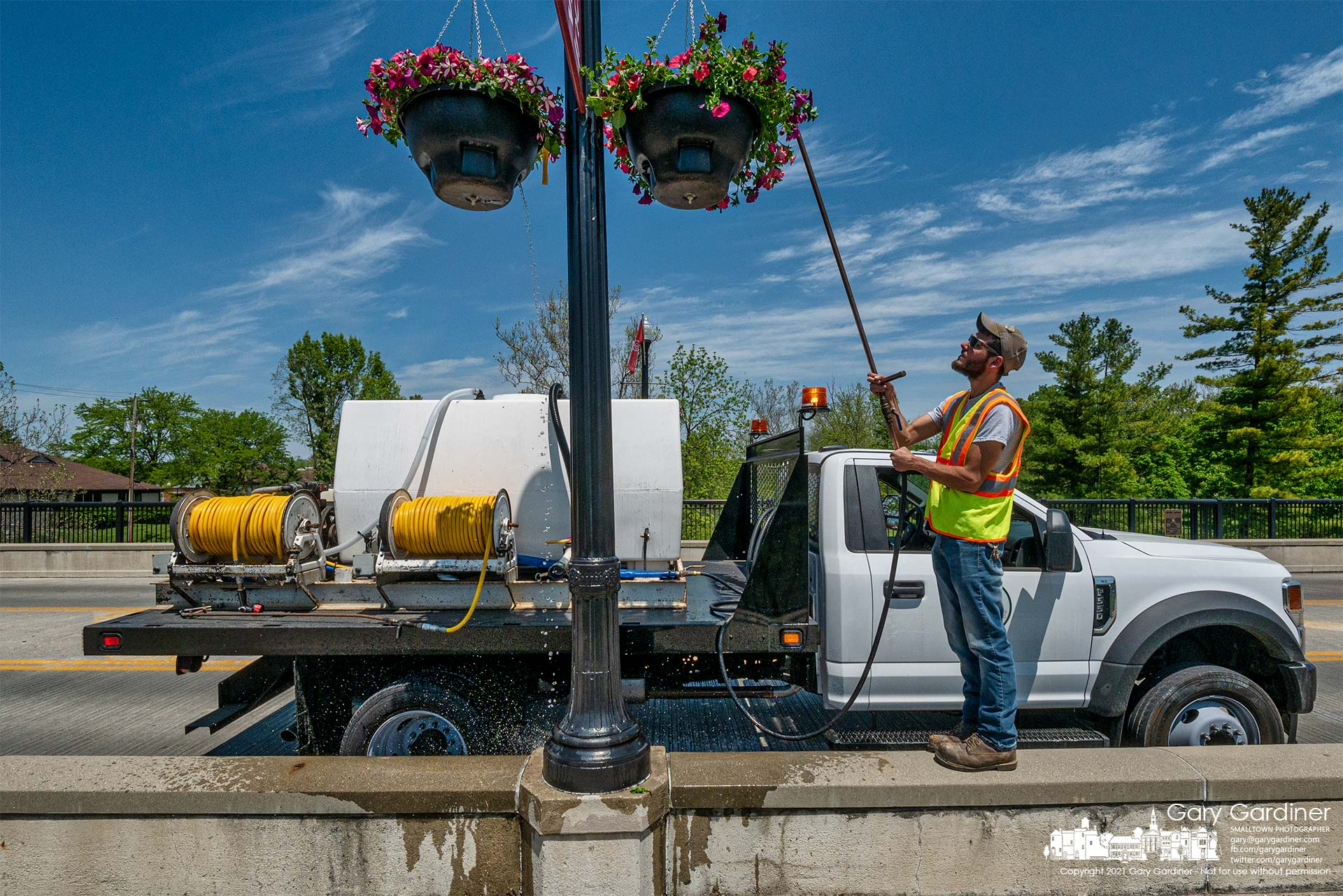 A city parks worker stands on the concrete barrier as he irrigates hanging baskets on the Main Street Bridge. My Final Photo for May 18, 2021.
