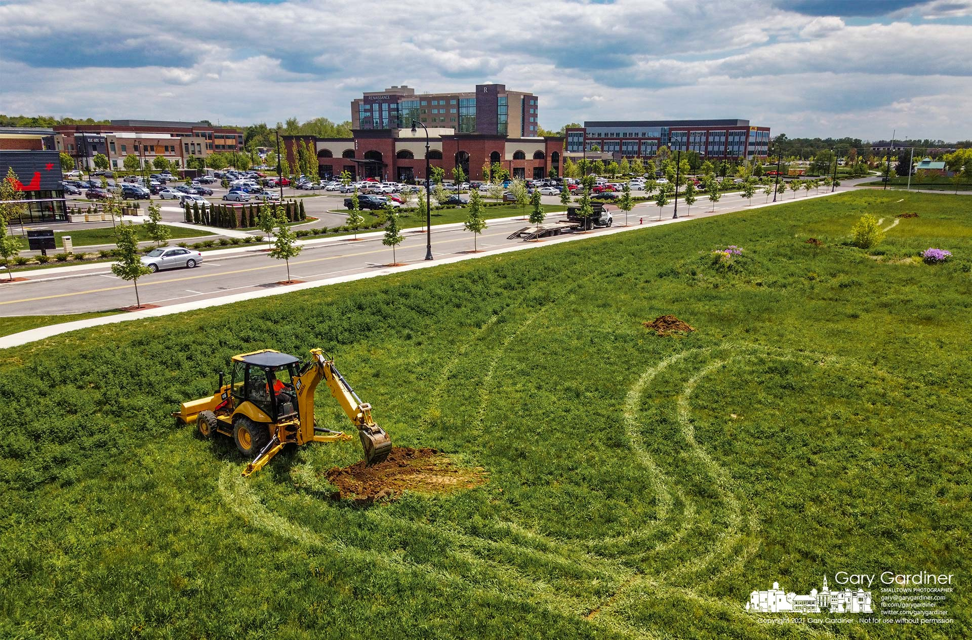 A back-hoe operator fills one of the test trenches dug into an undeveloped section of Westar at the corner of Cleveland and Polaris where developers are exploring new business construction. My Final Photo for May 14, 2021.