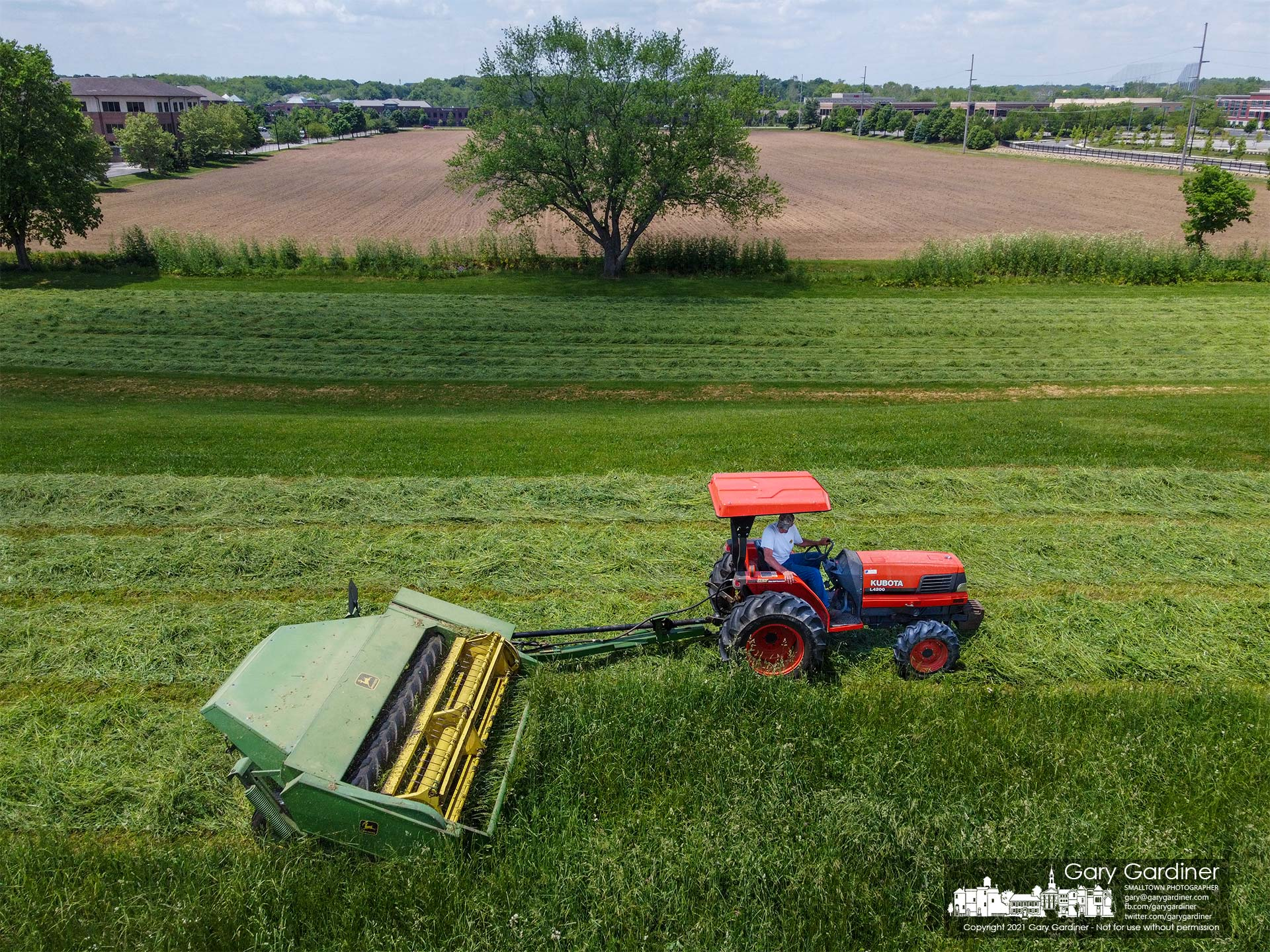 Duane Yarnell mows hay behind his barns and just above the large field recently planted with corn. My Final Photo for May 23, 3021.