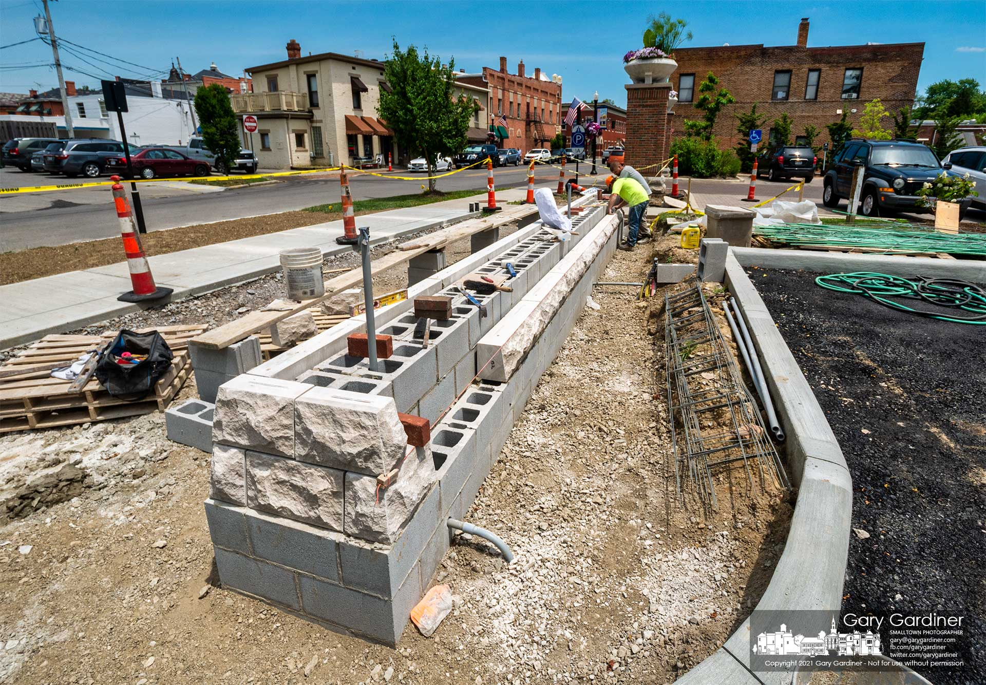 Masons install decorative sections of concrete that are the base for the new pillars and planters that will sit at the entrance of the new parking lot behind city hall. My Final Photo for June 24, 2021.