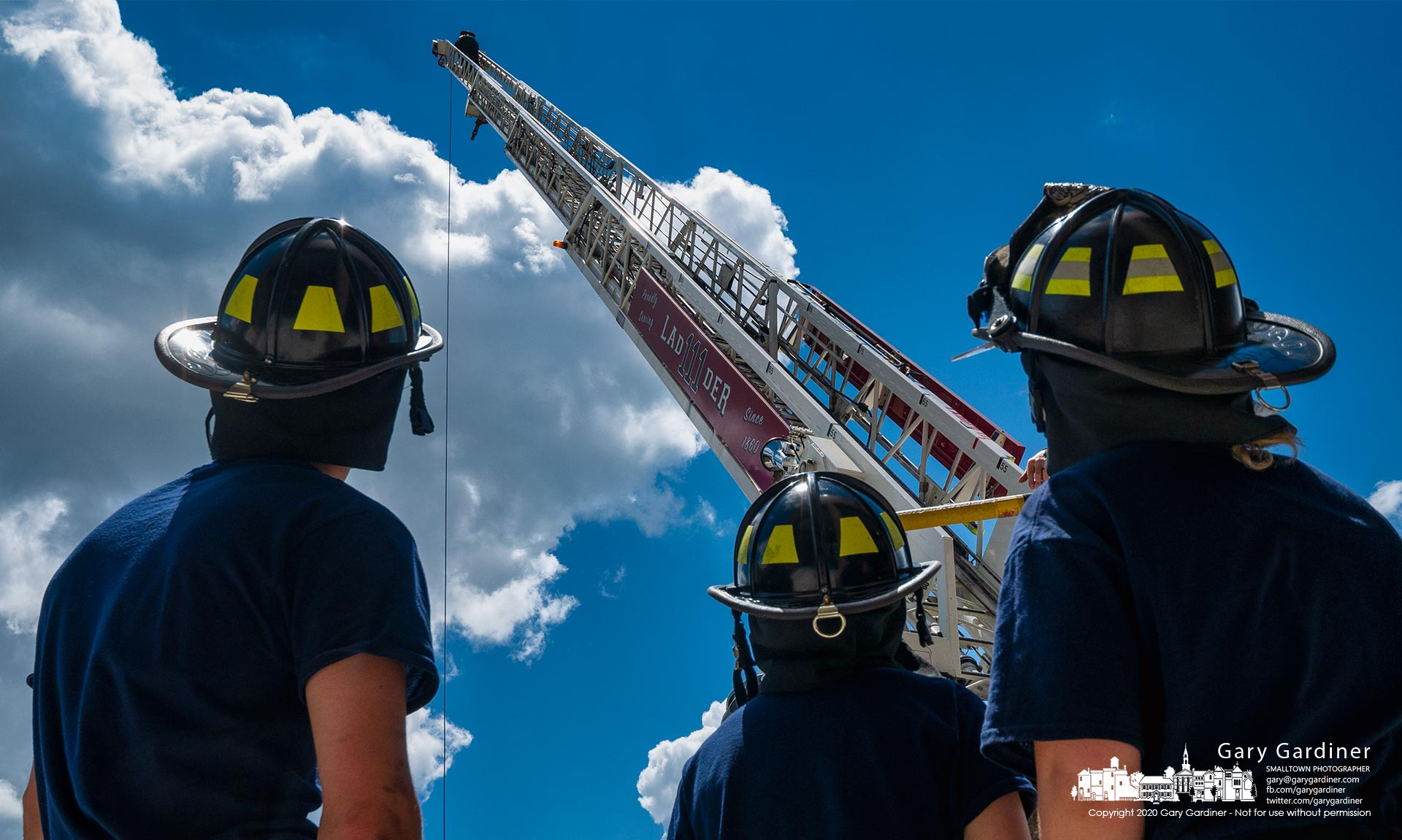 Firefighter trainees watch as another student reaches the top of a 105-foot aerial ladder during training with the climb being the final stage on their exam when training is completed. My Final Photo for june 15, 2021.