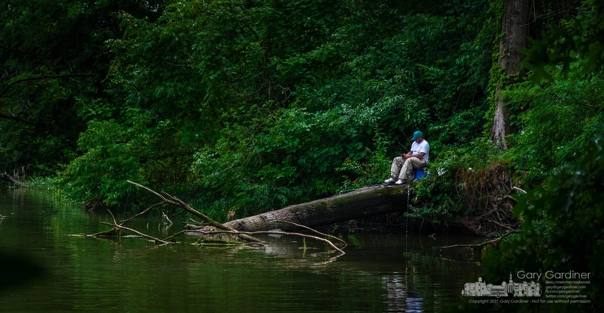 A fisherman resets his bait from his perch on a fallen tree along the shoreline of rain-swollen Hoover Reservoir. My Final Photo for June 30, 2021.