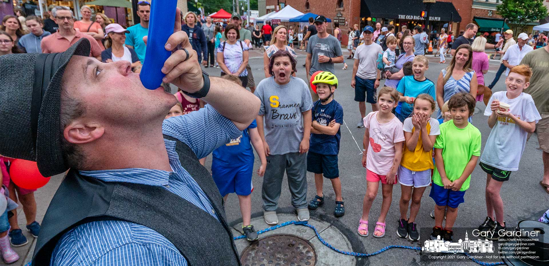A group of children watches in awe as Magic Nate mysteriously devours a balloon during one of his shows at the first Fourth Friday in Uptown Westerville for 2021. My Final Photo for June 25.