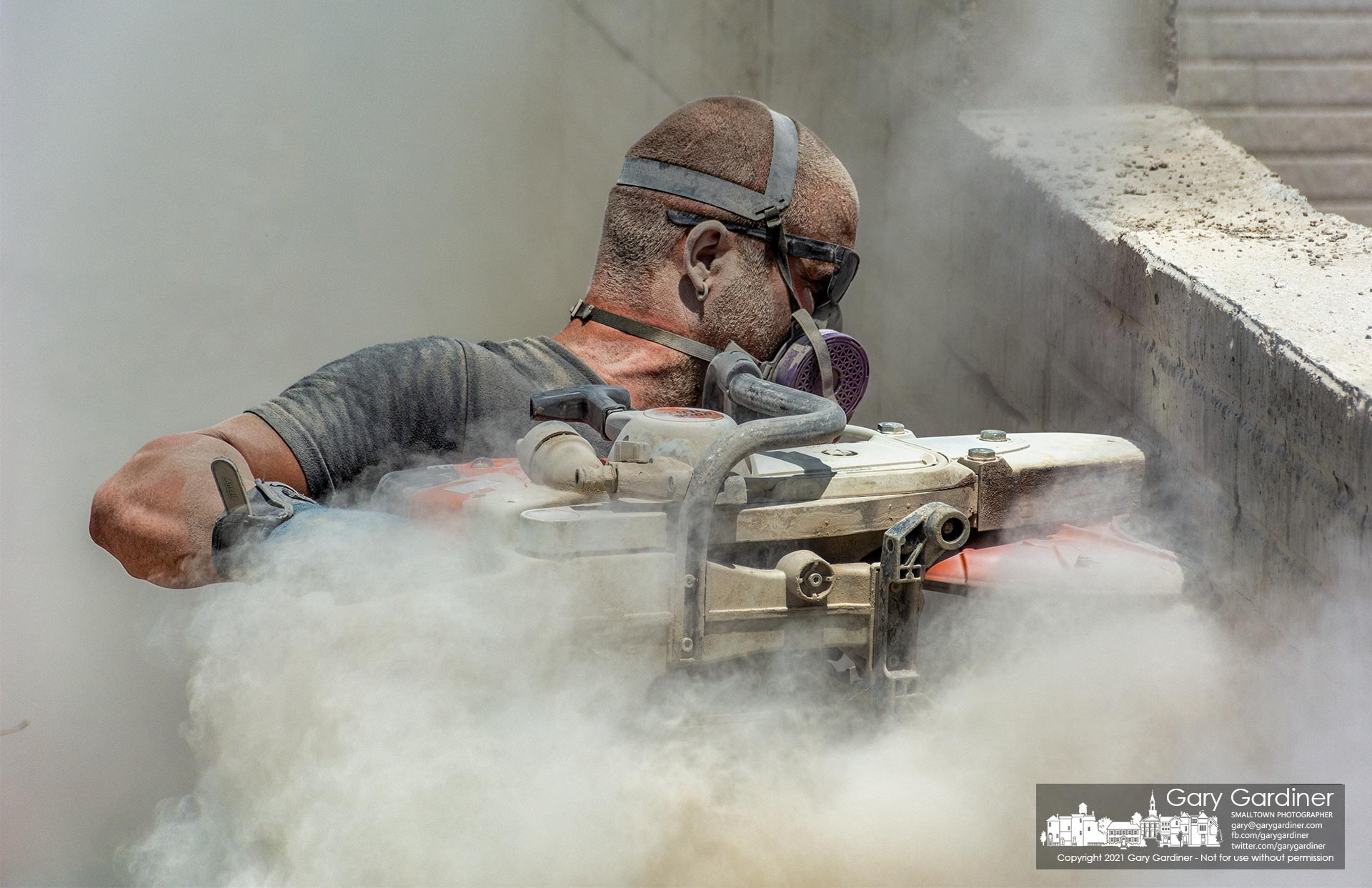 A contractor works through a cloud of dust thrown from the concrete wall he's cutting on a newly poured wall at a home under construction on East Walnut St. My Final Photo for June 29, 2021.