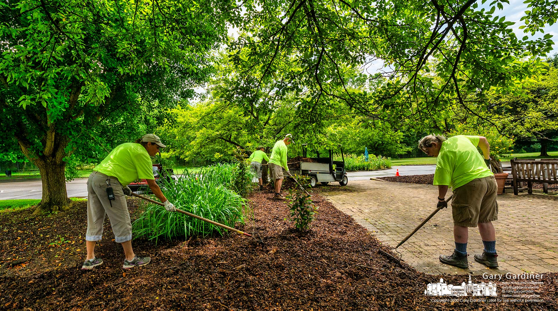 An Inniswood Metro Gardens grounds crew spreads mulch around the trees at the center of the parking lot. My Final Photo for June 18, 2021.