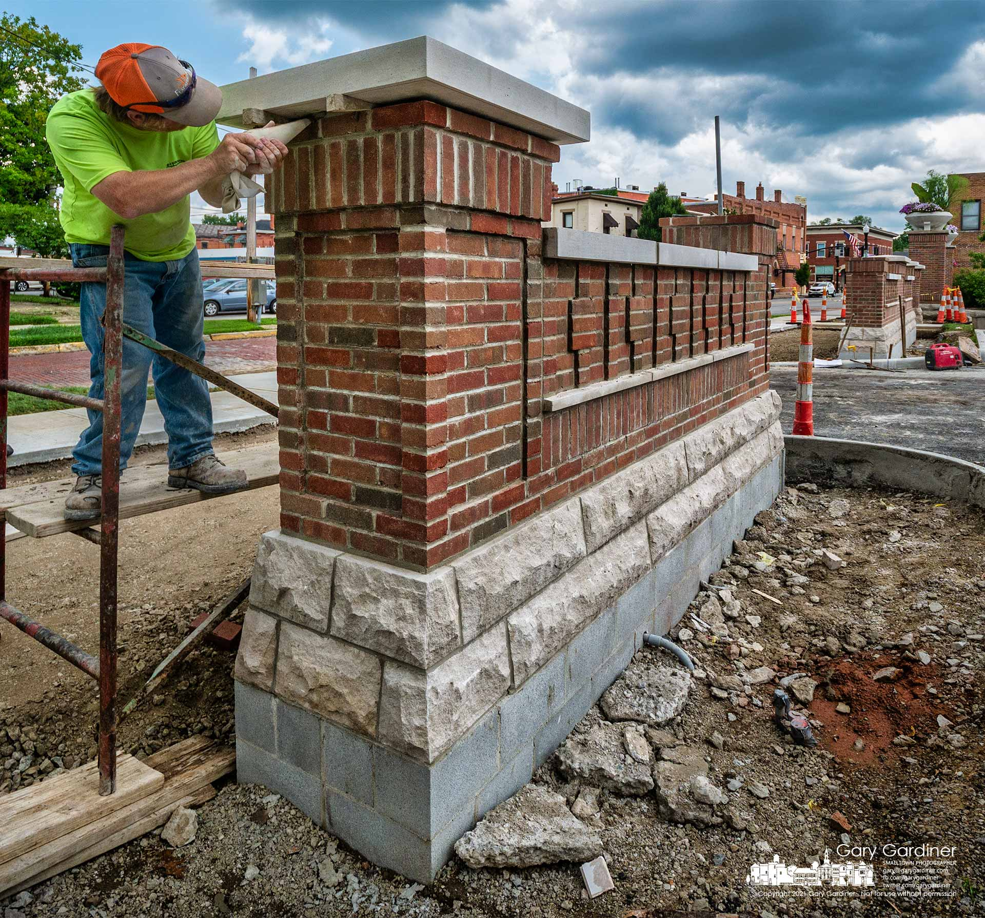 A brick mason squeezes fast-drying mortar into the gaps between the brick post and a concrete platform lowered onto it at the entrance to the new parking lot behind city hall. My Final Photo for July 14, 2021.
