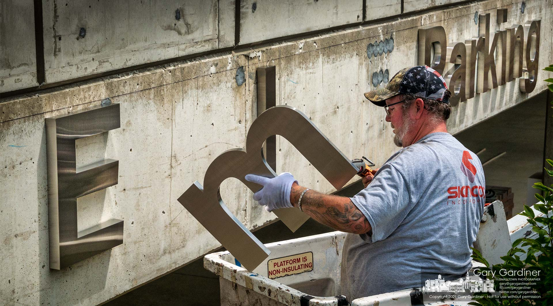 """A signmaker applies adhesive to the letter """"m"""" before attaching it next to the capital """"E"""" to create signage for the employee parking entrance at the COPC building on Africa Road. My Final Photo for July 16, 2021."""