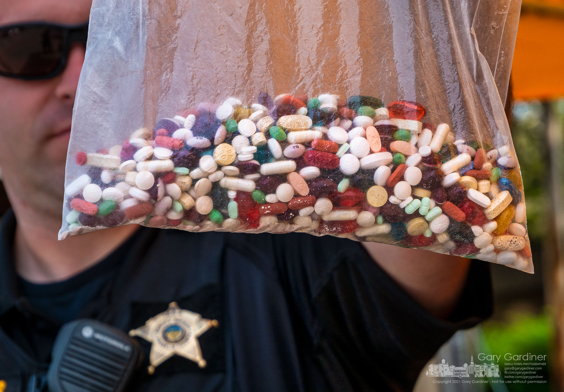 A Franklin County Deputy Sheriff holds a plastic bag containing unused, expired, or not needed prescription and over-the-counter drugs dropped off in the drive-thru at the Kroger on Schrock Road during Saturday's event sponsored by the Ohio Attorney General. My Final Photo for July 31, 2021.