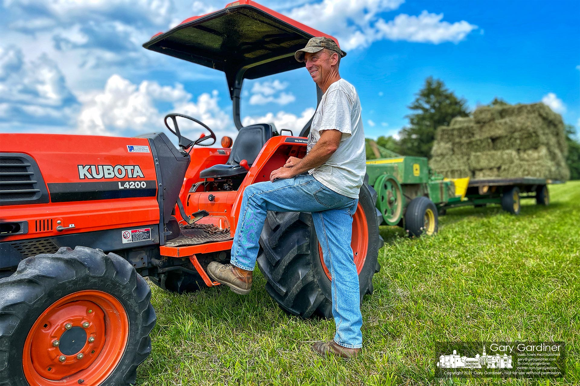 Duane Yarnell pauses before completing baling hay in the field along the edge of his farmland on County Line Road. My Final Photo for July 7, 2021.