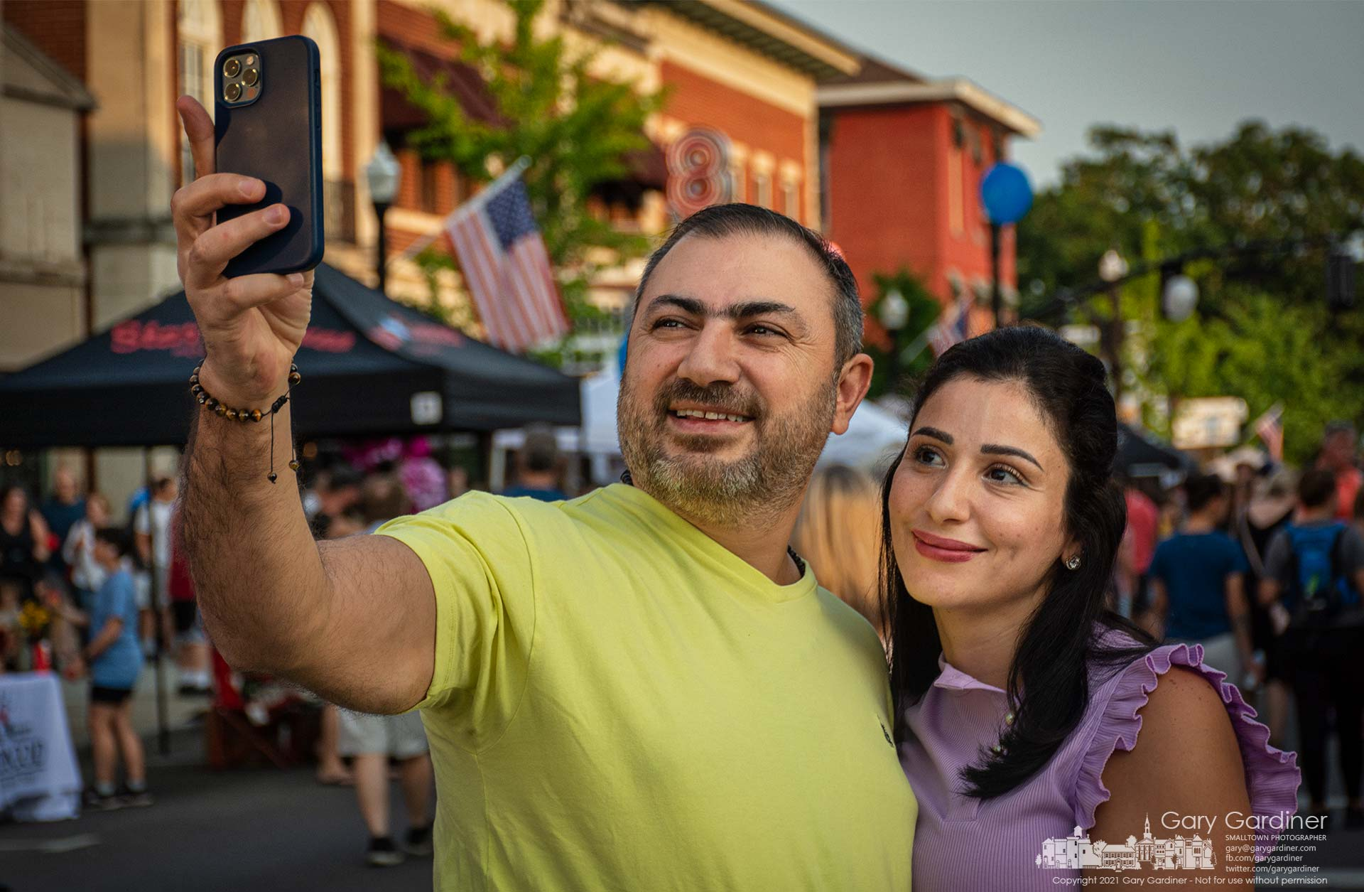 A couple pauses to photograph themselves with their smartphone in the middle of the intersection of State and Main during Fourth Friday in Westerville. My Final Photo for July 23, 2021.