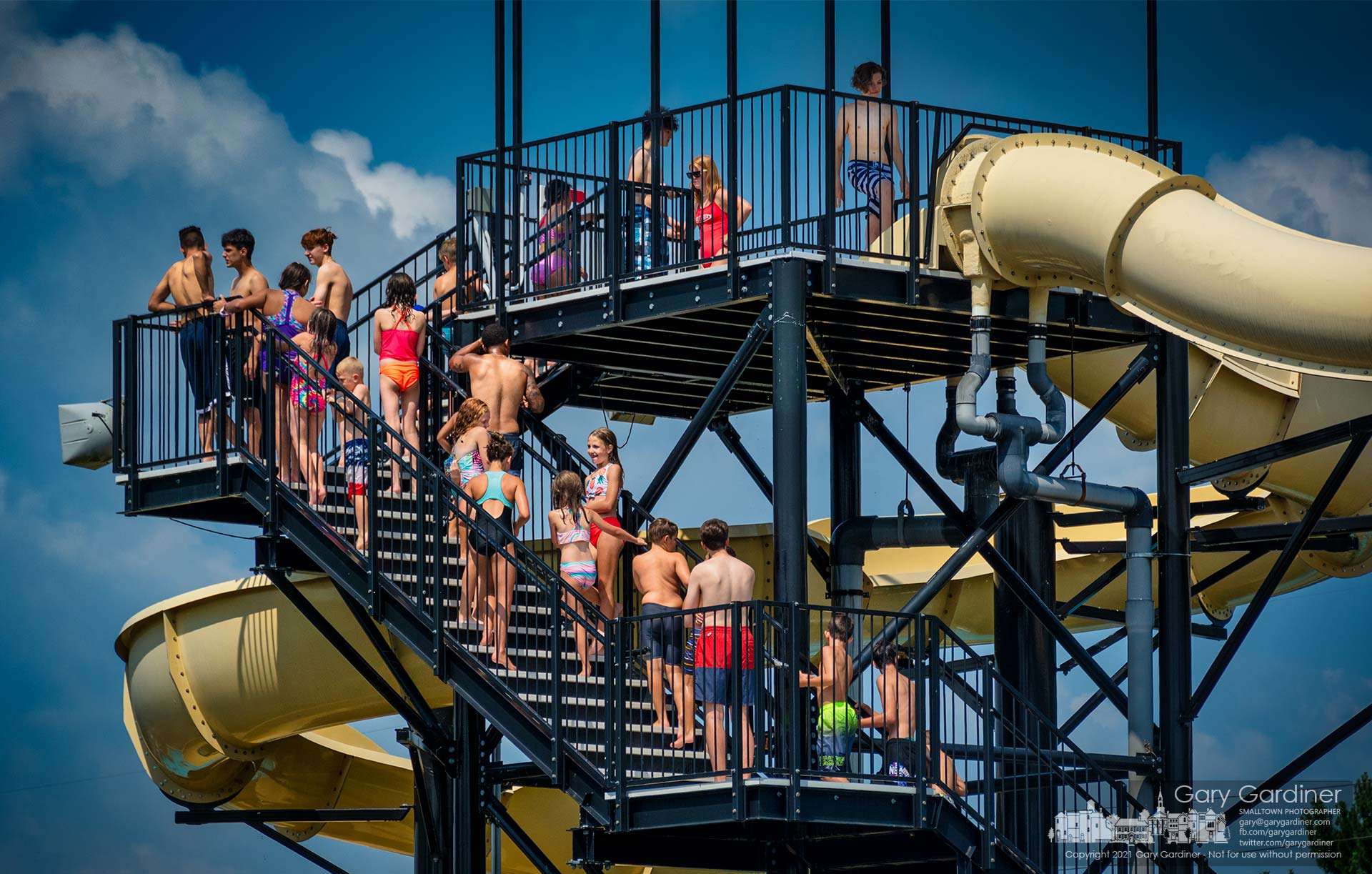 Youngsters line up on stairs leading to the two water slides at Highlands Aquatic Center hoping their time arrives for the fun ride before the pools close for 15 minutes before the hour. My Final Photo for July 18, 2021.