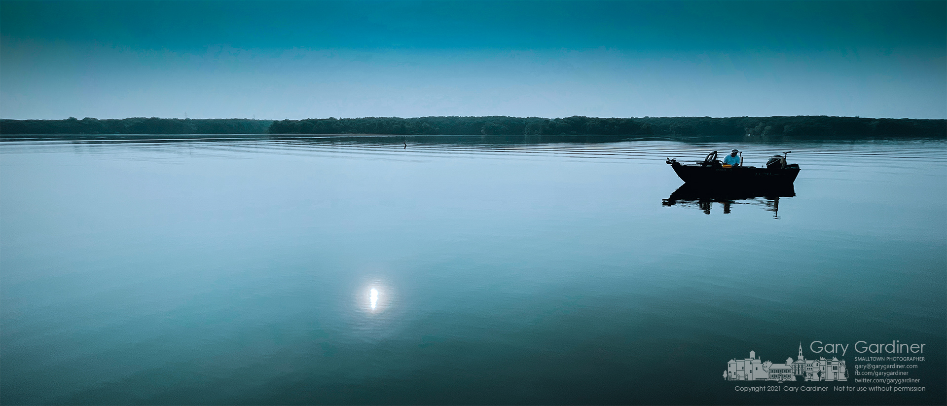 A fisherman sits idle on the Hoover Reservoir, its still waters disturbed only by his return to the docks after an early morning fishing. My Final Photo for July 28, 2021.