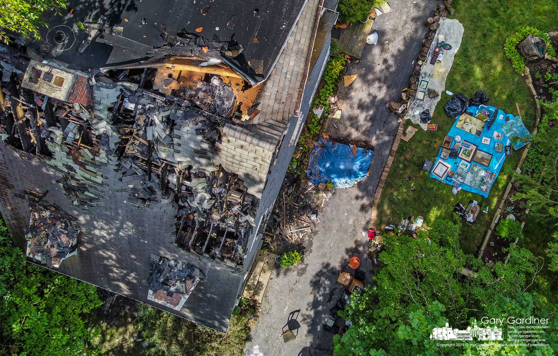 A portion of a family's collection of art and personal belongings are spread out on tarps beside their damaged home after an overnight fire they say started with an overheated lithium-ion battery charger. My Final Photo for July 2, 2021.