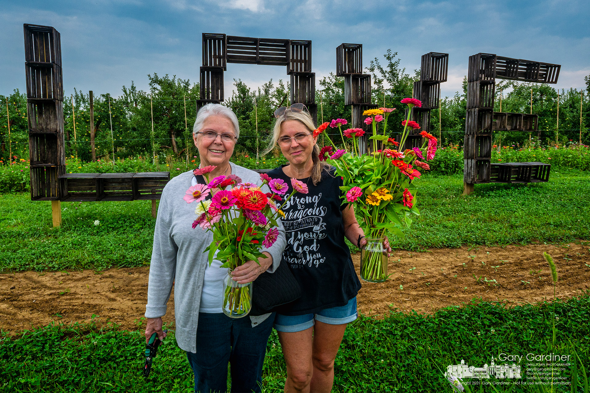 """A mother and daughter pose in front of a """"Love"""" sign sculpted from fruit boxes after having picked flowers at Branstools Orchard in Utica. My Final Photo for July 29, 2021."""