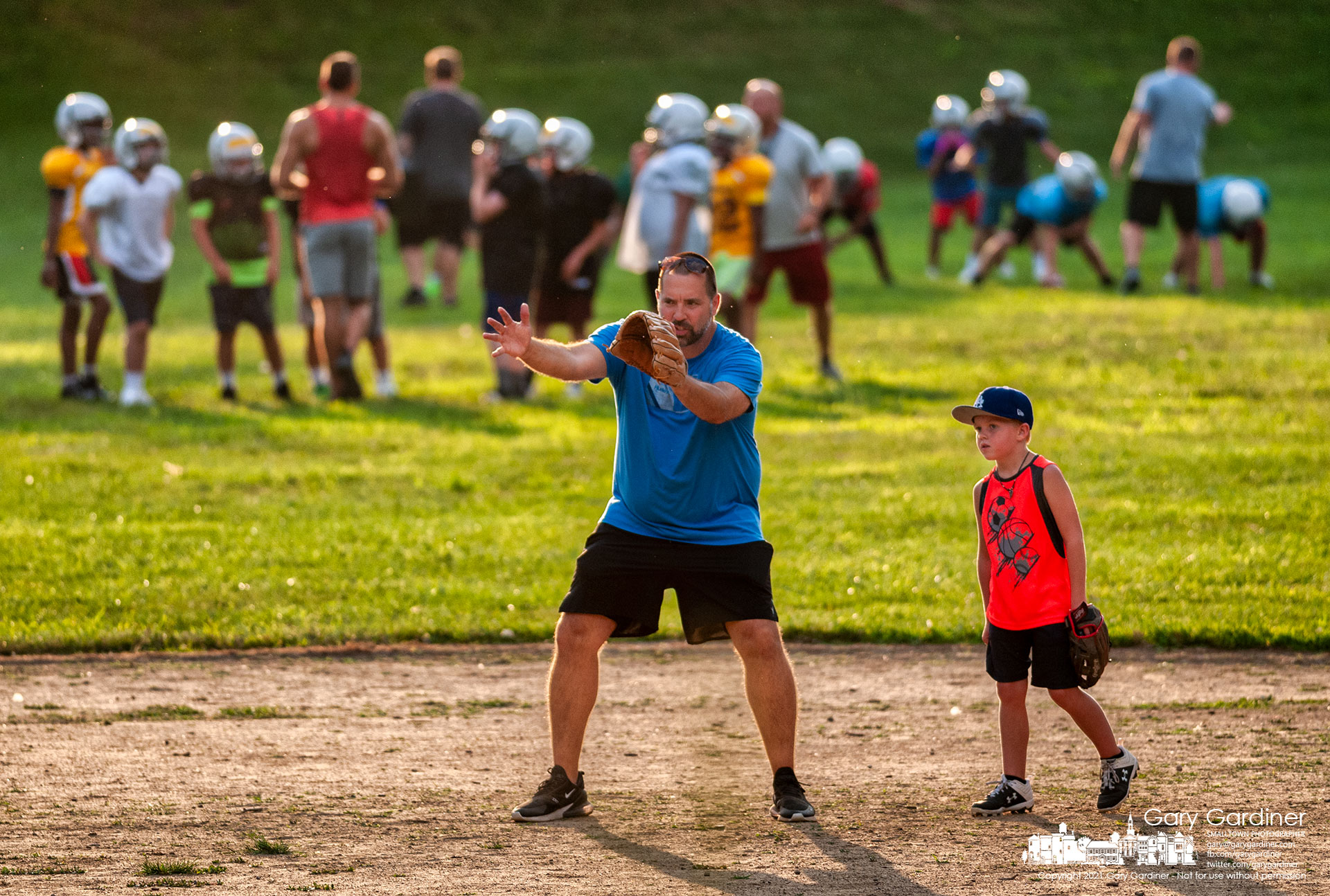 A baseball coach instructs one of his players at Alum Creek Park where other coaches work with the football team practicing at the other end of the field. My Final Photo for Aug. 5, 2021.