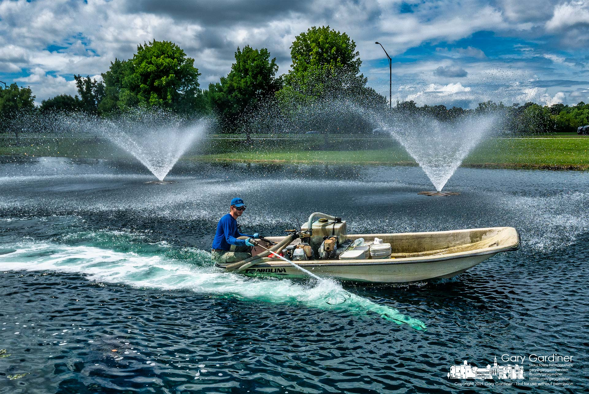 A contractor travels around the pond in front of the Community Center spraying copper sulfate into the water to kill the algae bloom. My Final Photo for Aug. 18, 2021.