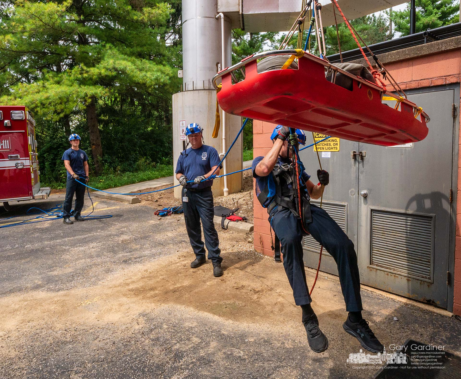 A Westerville firefighter hangs from rescue equipment attached to the top of the Otterbein University service department building during an afternoon training class. My Final Photo for Aug. 11, 2021.