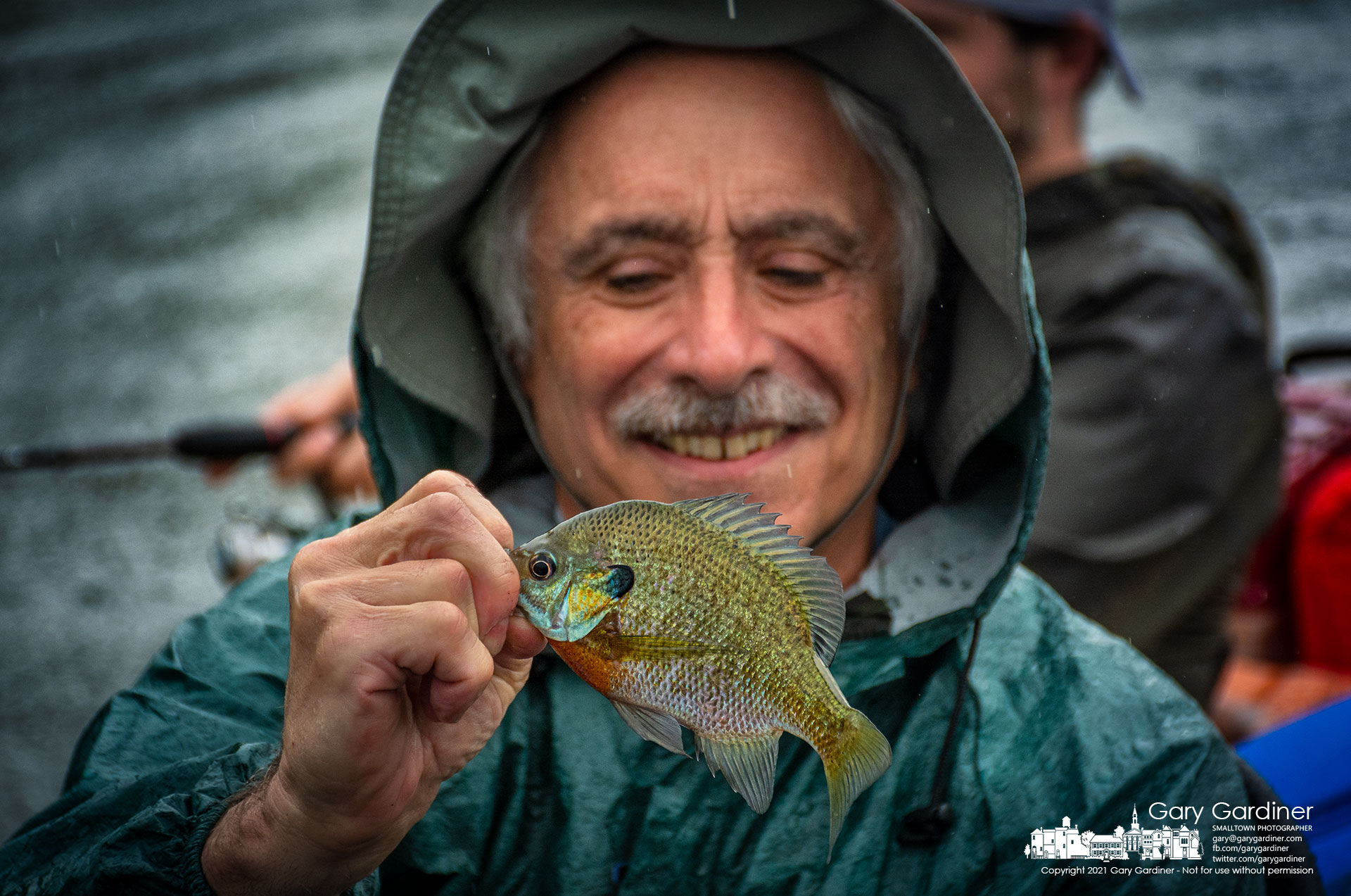 A fisherman admires one of the smaller bluegills he pulled in from a lagoon on the western edge of Hoover Reservoir during Tuesday's almost constant rain showers. My Final Photo for Aug. 17, 2021.
