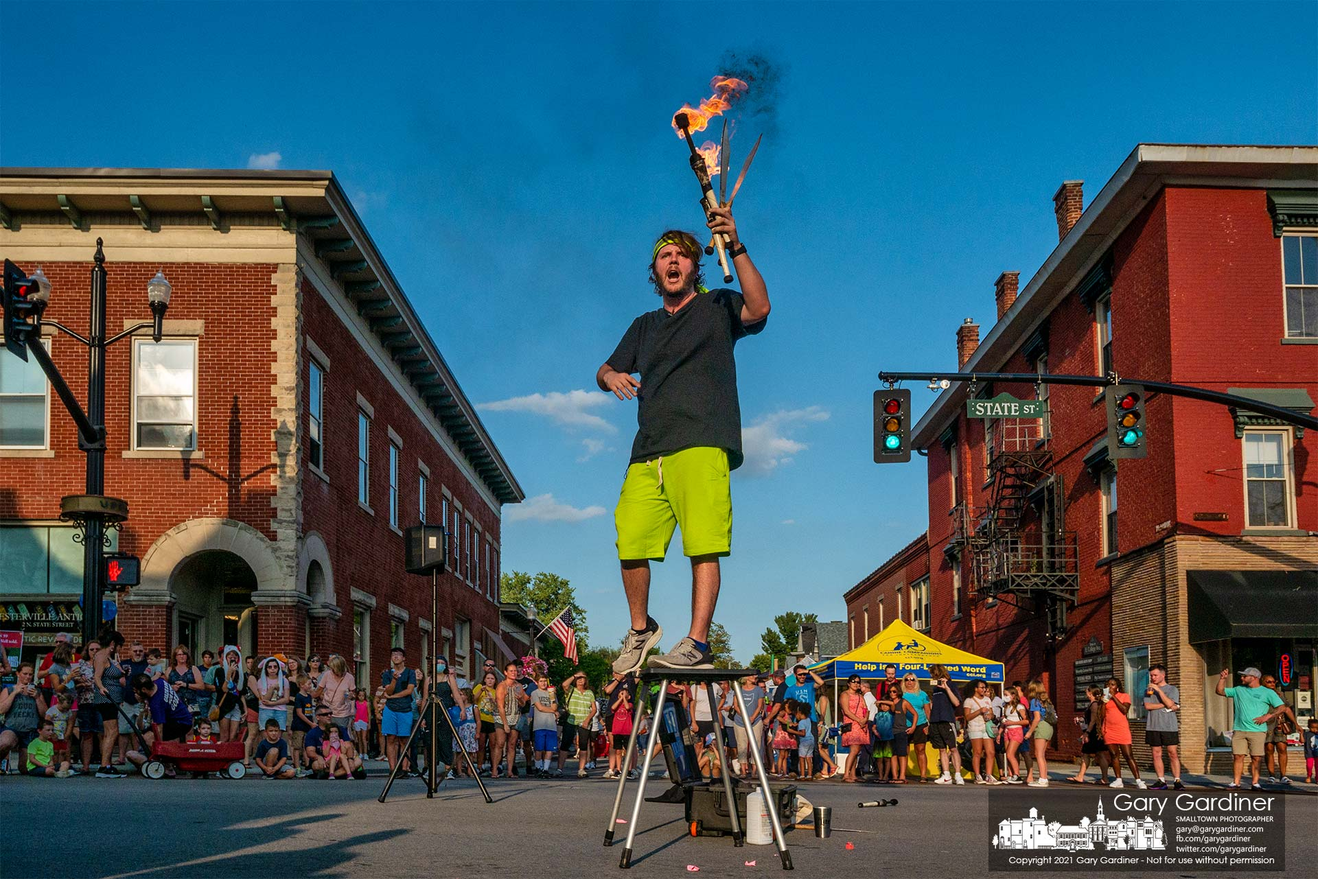 A juggler bearing large knives and flaming batons performs at the center of State and College as part of the Fourth Friday entertainment in Uptown Westerville. My Final Photo for Aug. 27, 2021.