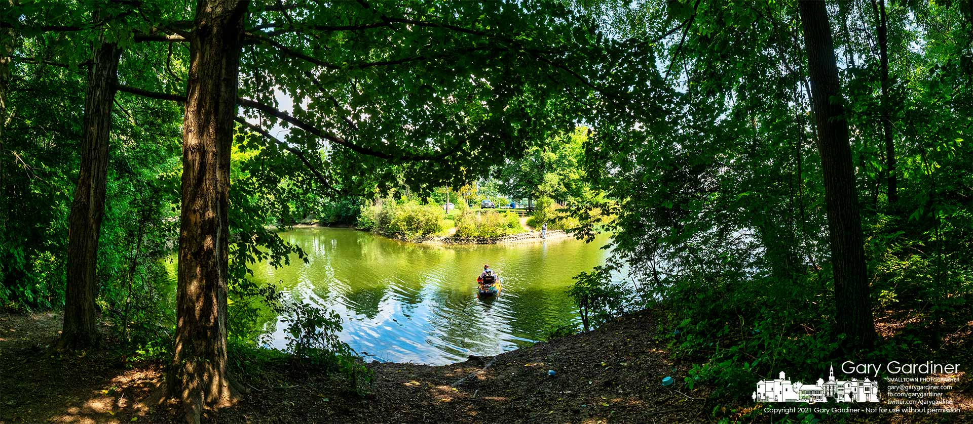 A fisherman steadies his kayak beside the shadows from the tree-lined shoreline in shallow waters on the edge of Hoover Reservoir. My Final Photo for Aug. 20, 2021.