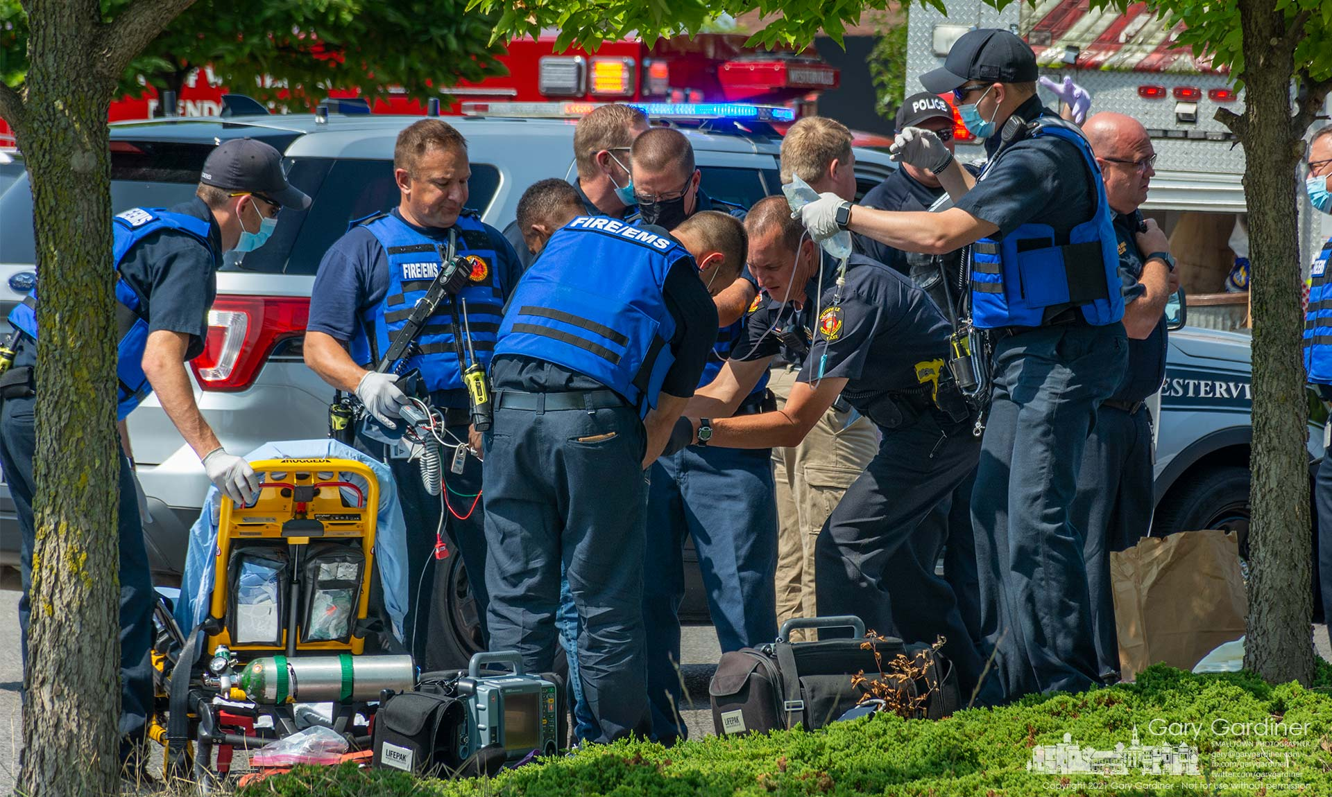 A Westerville police officer searches a man being treated for a stab wound by fire department medics after a fight in a shopping center parking lot Monday morning. My Final Photo for Aug. , 2021.