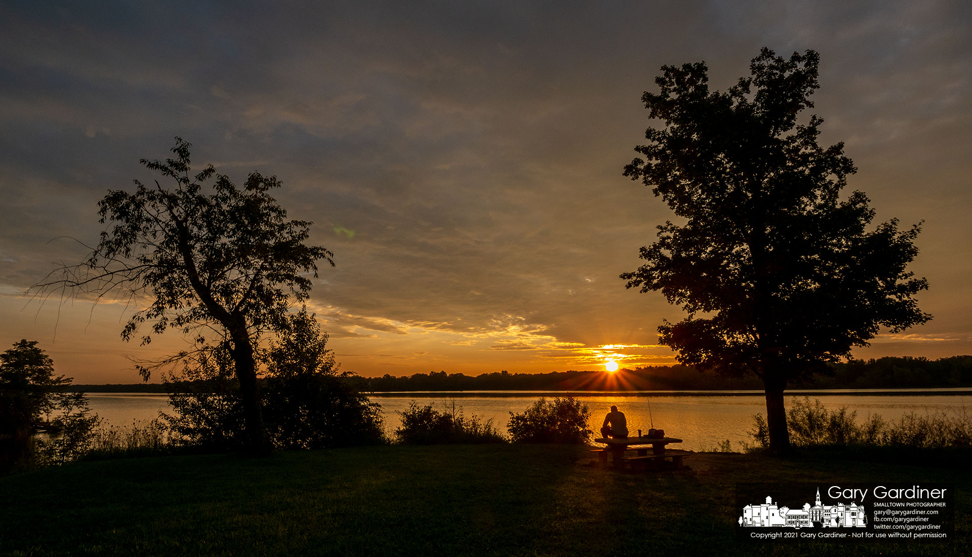 A fisherman watches his lines and the sunrise over the trees from his perch on the picnic table at the edge of Hoover Reservoir at Red Bank Marina. My Final Photo for Aug. 28, 2021.