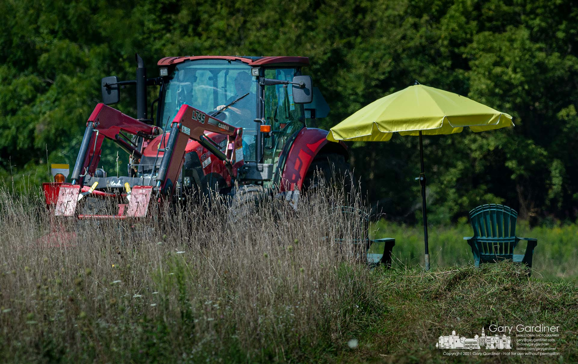 Kevin Scott steers his tractor around an umbrella and lawn chairs placed in an open space in the farm field he cutting for hay on North West Street. My Final Photo for Sept. 3, 2021.